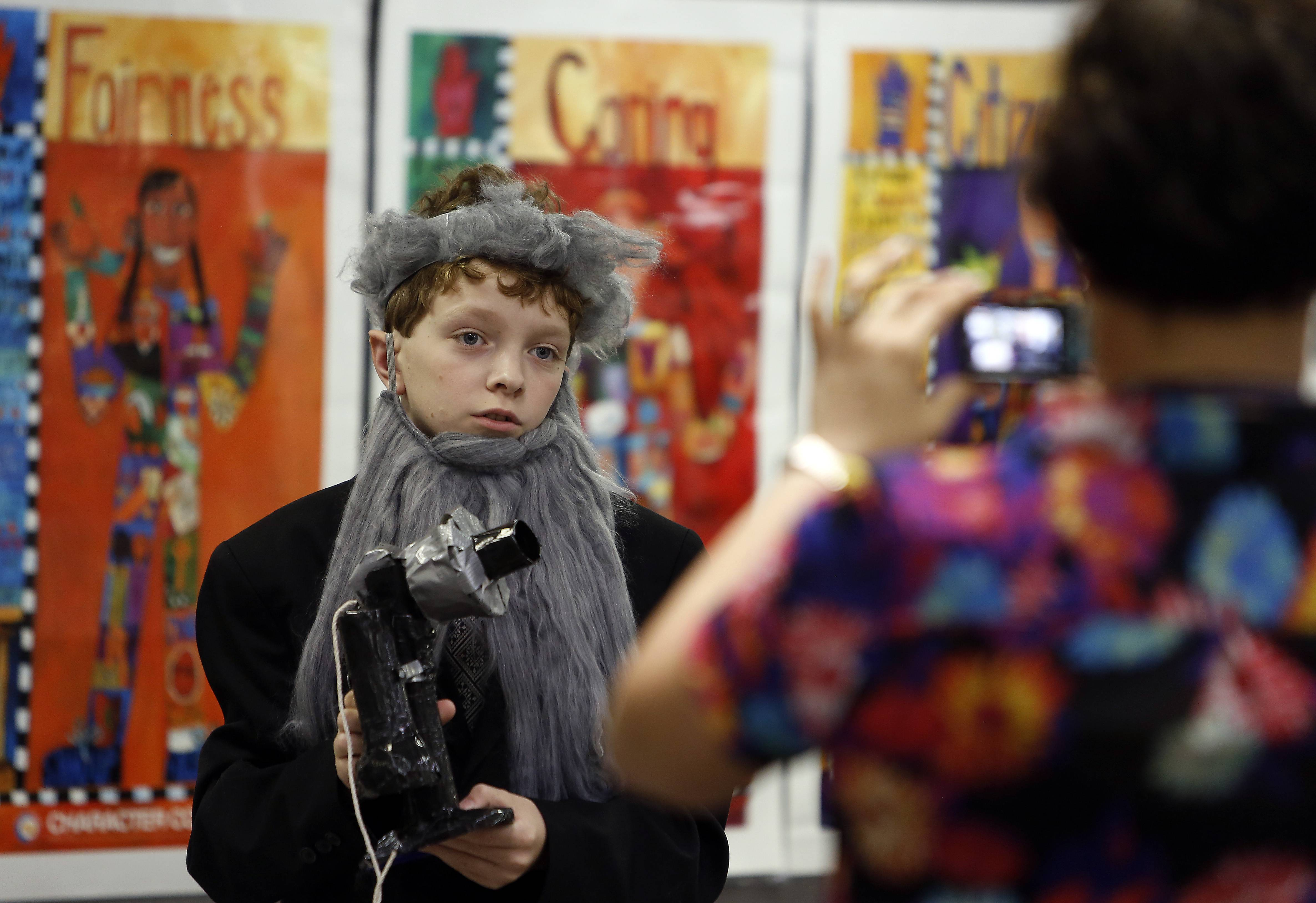 Fifth-grader Taylor Rodina, 10, portrays Alexander Graham Bell during Einstein Academy's wax museum project Tuesday at the Elgin school. Tyler is being video recorded by Cathy Ilani, Einstein Academy's founder.