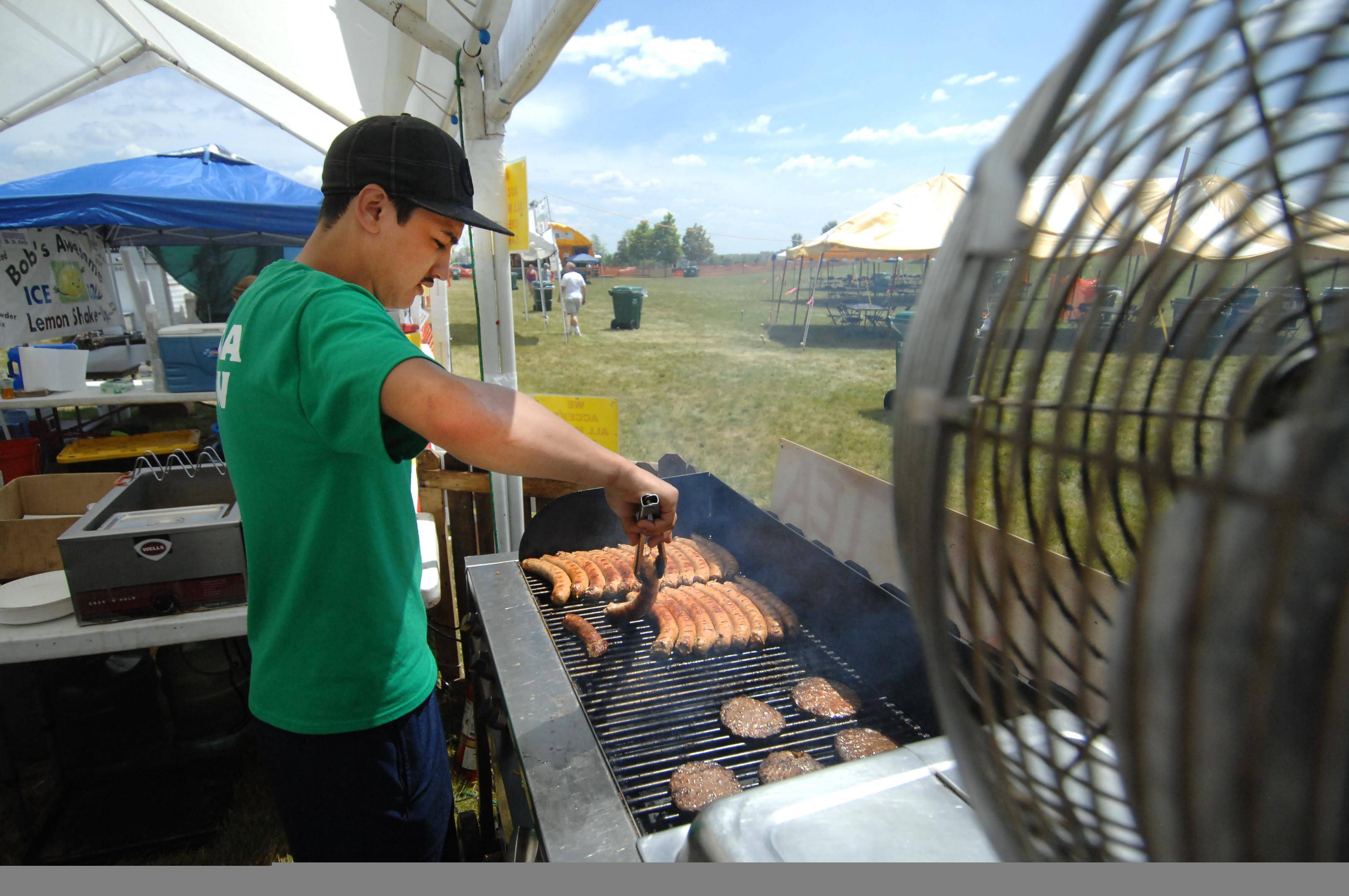 Danny Arroyo of Genoa Italian Concessions grills Italian sausage at a previous Gilberts Community Days festival.