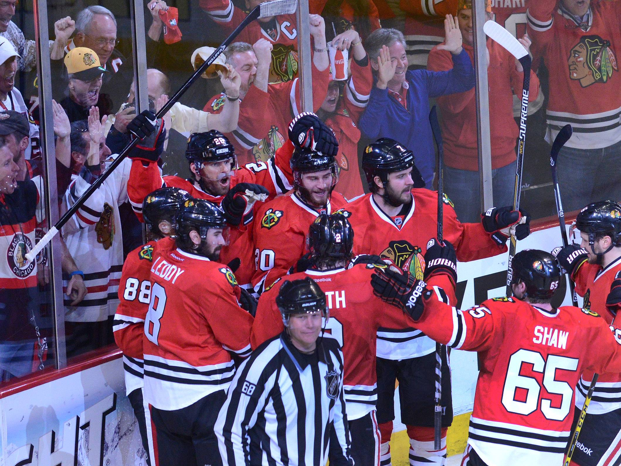 Chicago Blackhawks center Michal Handzus, left, celebrates a game winning goal with right wing Patrick Kaneand defenseman Nick Leddy, right, as Los Angeles Kings defenseman Slava Voynov, second from right, skates off during the second overtime period.