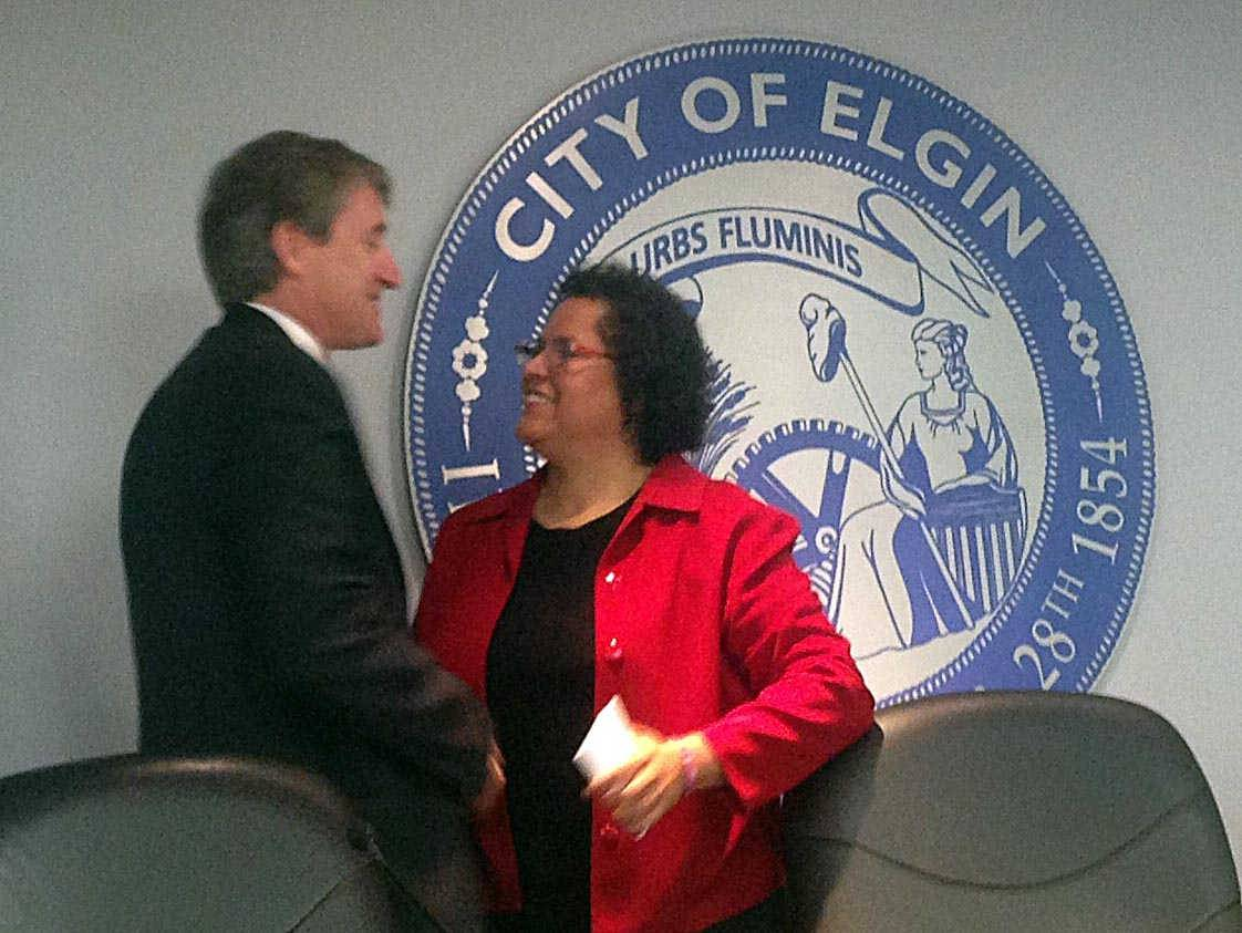 "Elgin City Councilman John Steffen, left, shakes the hand of Rosamaria ""Rose"" Martinez shortly after she was appointed to a vacant seat on the Elgin City Council on Wednesday night."