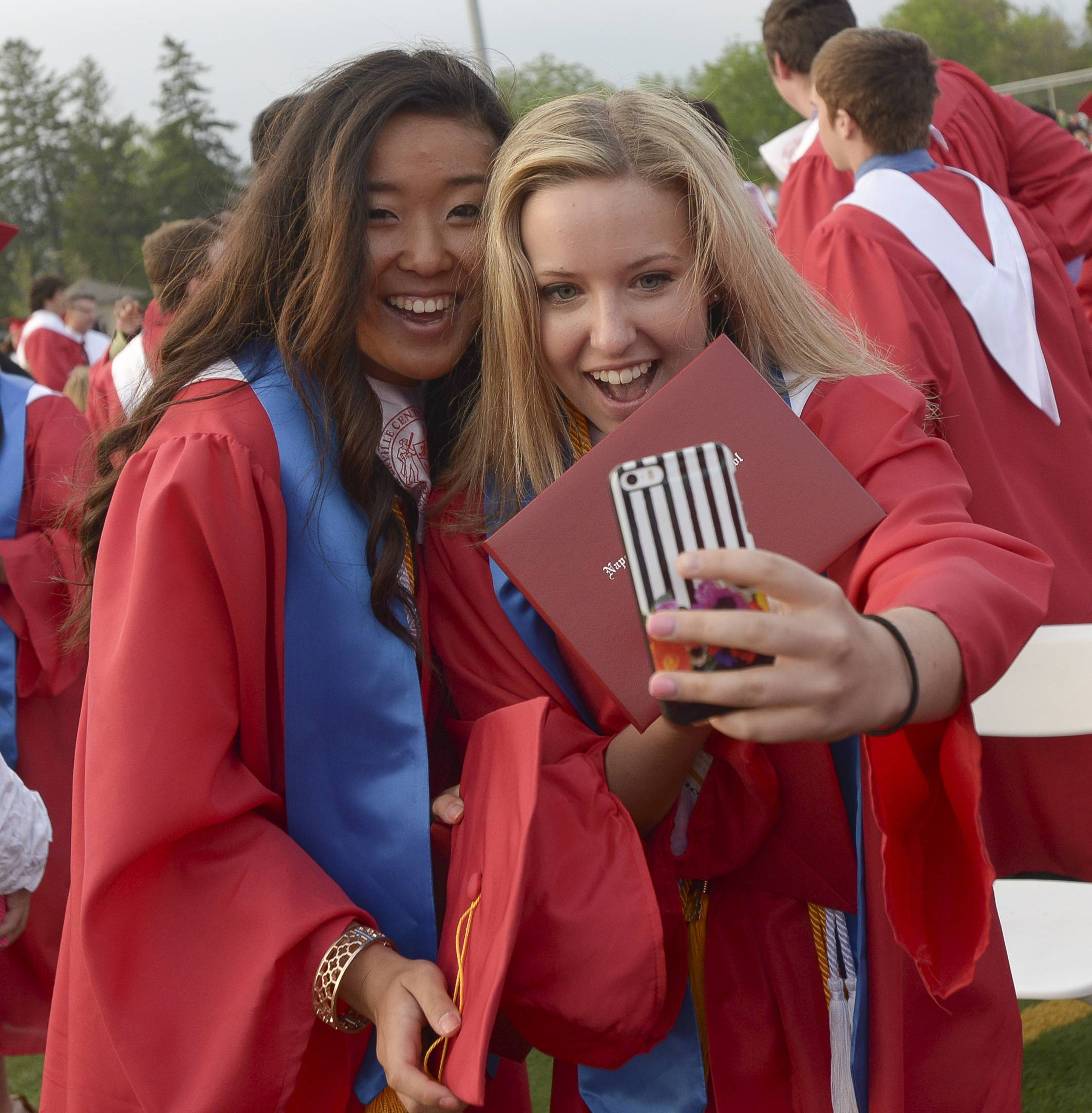 Grace Lee and Sarah Crotty take a selfie after the Naperville Central High School graduation Wednesday, May 28 at the school's football field.