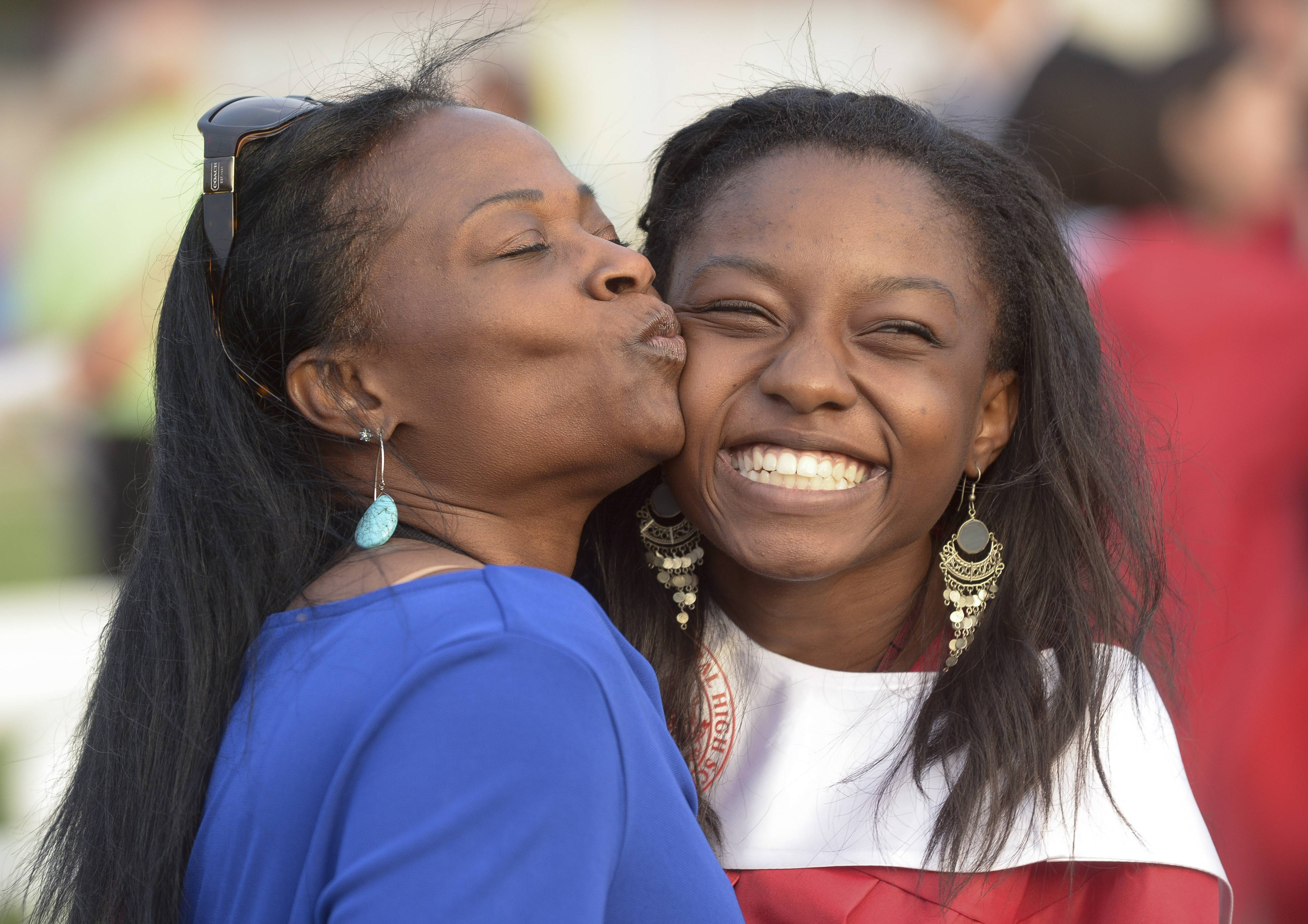 Mechelle Thomas gives her daughter Chelsea a kiss while having their photo taken, after the Naperville Central High School graduation Wednesday, May 28 at the school's football field.
