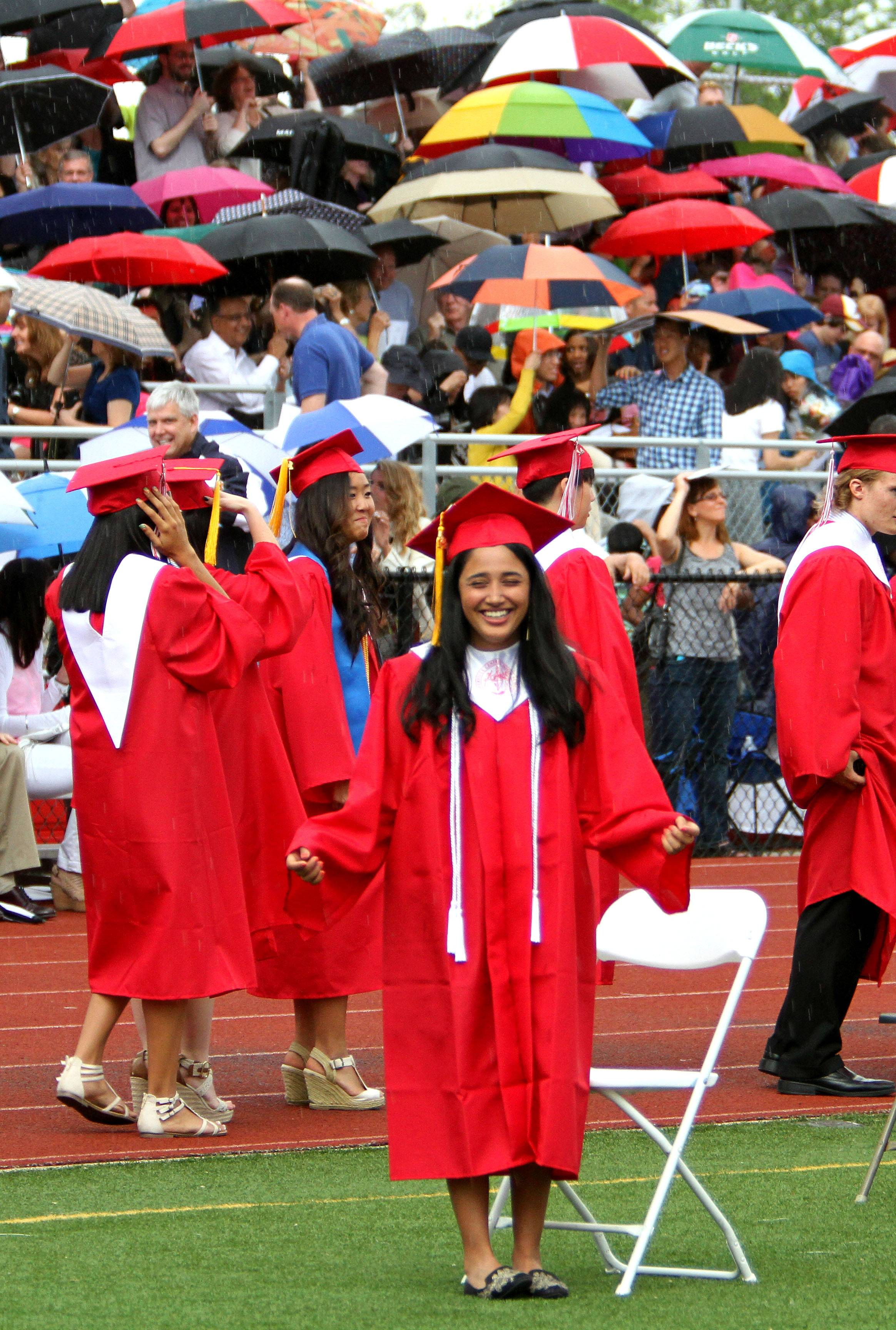 Akshada Apte reacts as it starts to rain at the start of the Naperville Central High School graduation ceremony on Tuesday, May 27, soon after lightning was seen and the cermony had to be postponed until Wednesday, May 28  at 6pm.