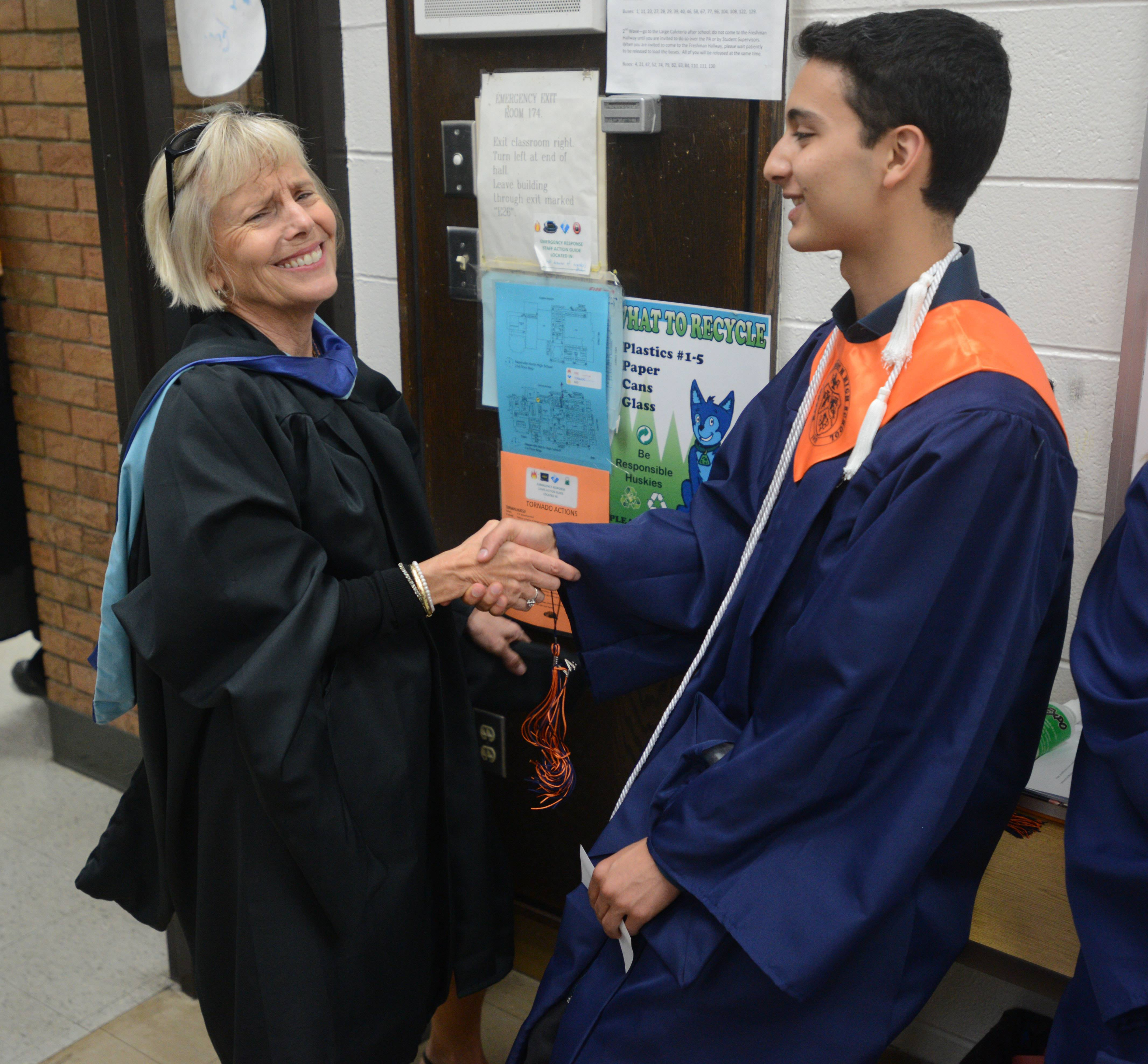 Spanish teacher Emily Bishop congratulates Juan Jara,17, of Naperville before the start of  the Naperville North High School graduation Wednesday.