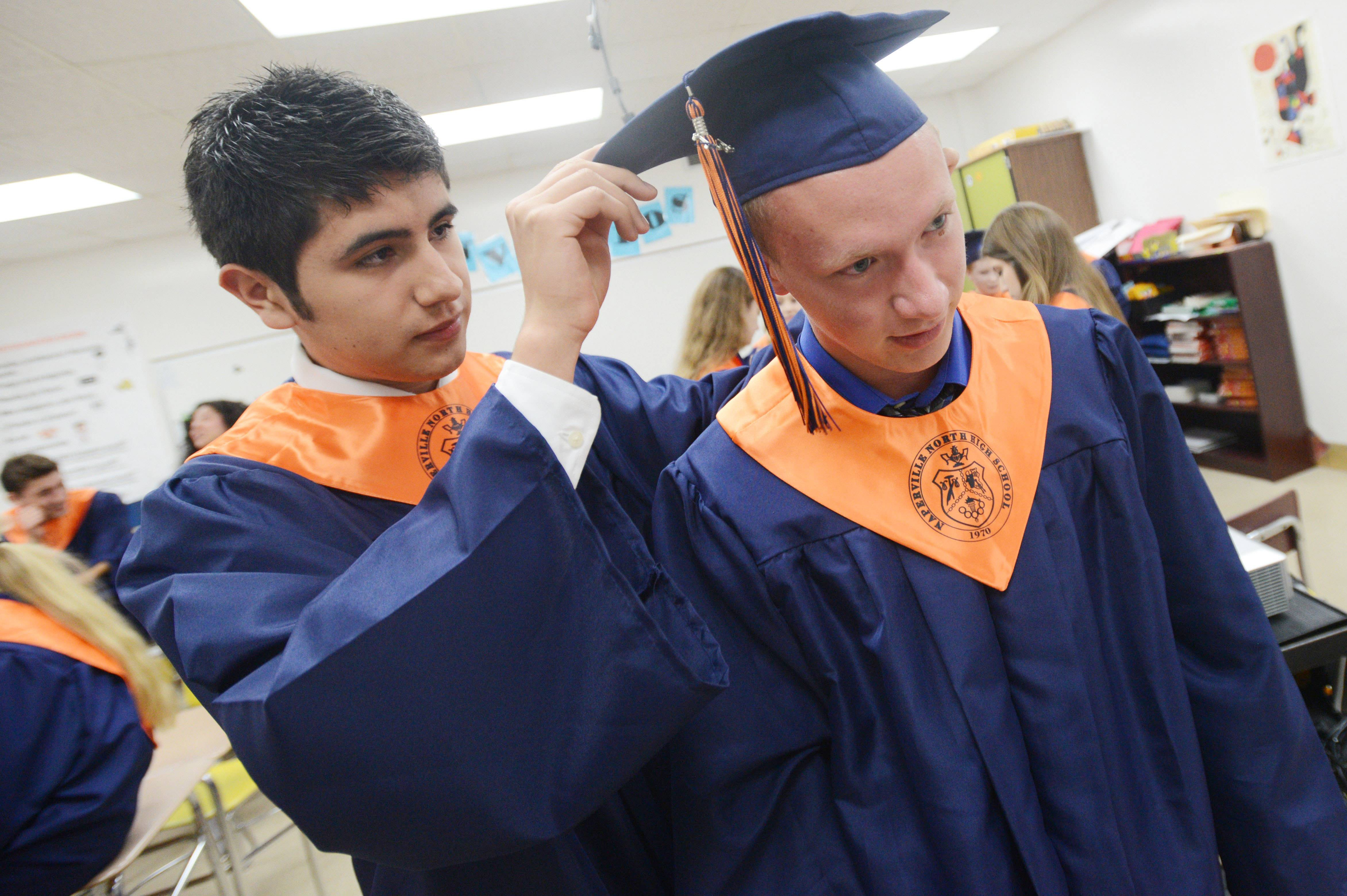 Francisco Espino,17, of Naperville helps Colin Edgington,17, of Naperville with his hat before the start of the Naperville North High School graduation Wednesday.
