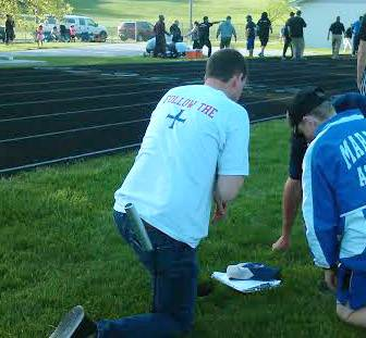 Marmion coaches kneel as first responders in the background tend to injured Marmion coach Ed DeGeeter moments after he was struck in the head by a 12-pound shot put Friday at Memorial Field in Elgin.