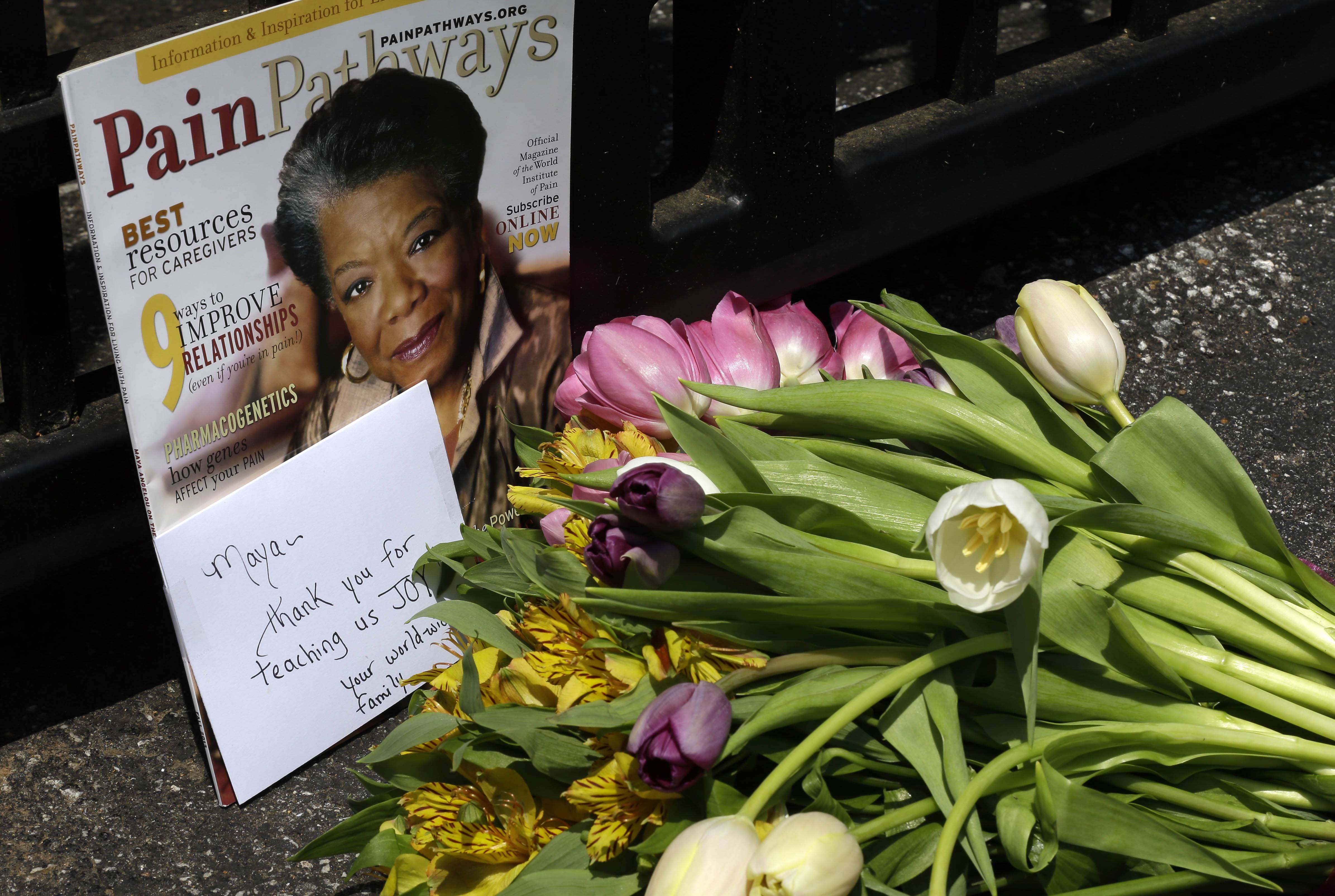 A bouquet of flowers and a magazine showing Maya Angelou on the cover lies outside a gate at the home of Angelou in Winston-Salem, N.C., Wednesday, May 28, 2014. Angelou, a Renaissance woman and cultural pioneer, has died, Wake Forest University said in a statement Wednesday. She was 86.
