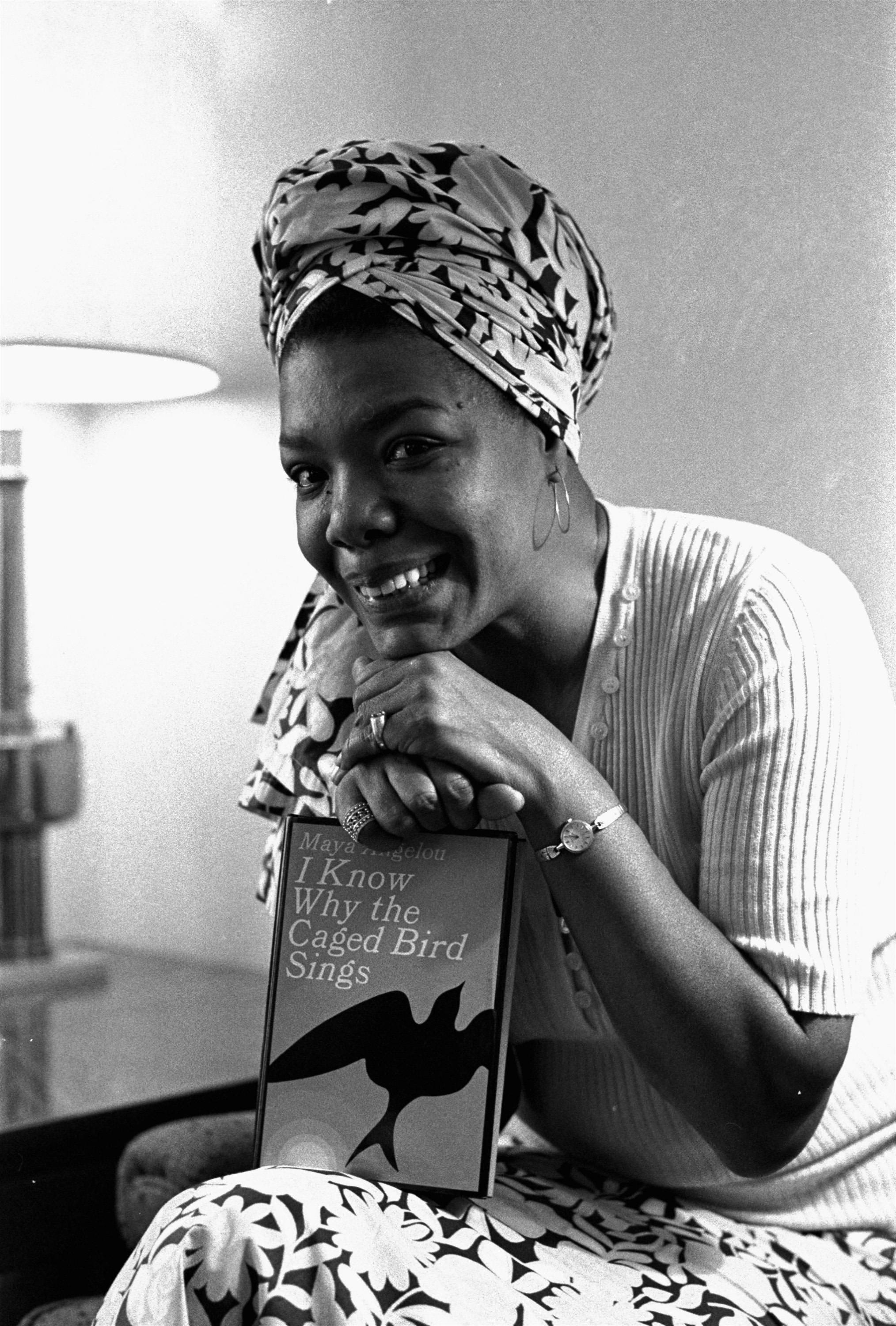 "Maya Angelou poses with a copy of her book, ""I Know Why the Caged Bird Sings,"" in Los Angeles. Angelou, a Renaissance woman and cultural pioneer, has died, Wake Forest University said in a statement Wednesday, May 28, 2014. She was 86."
