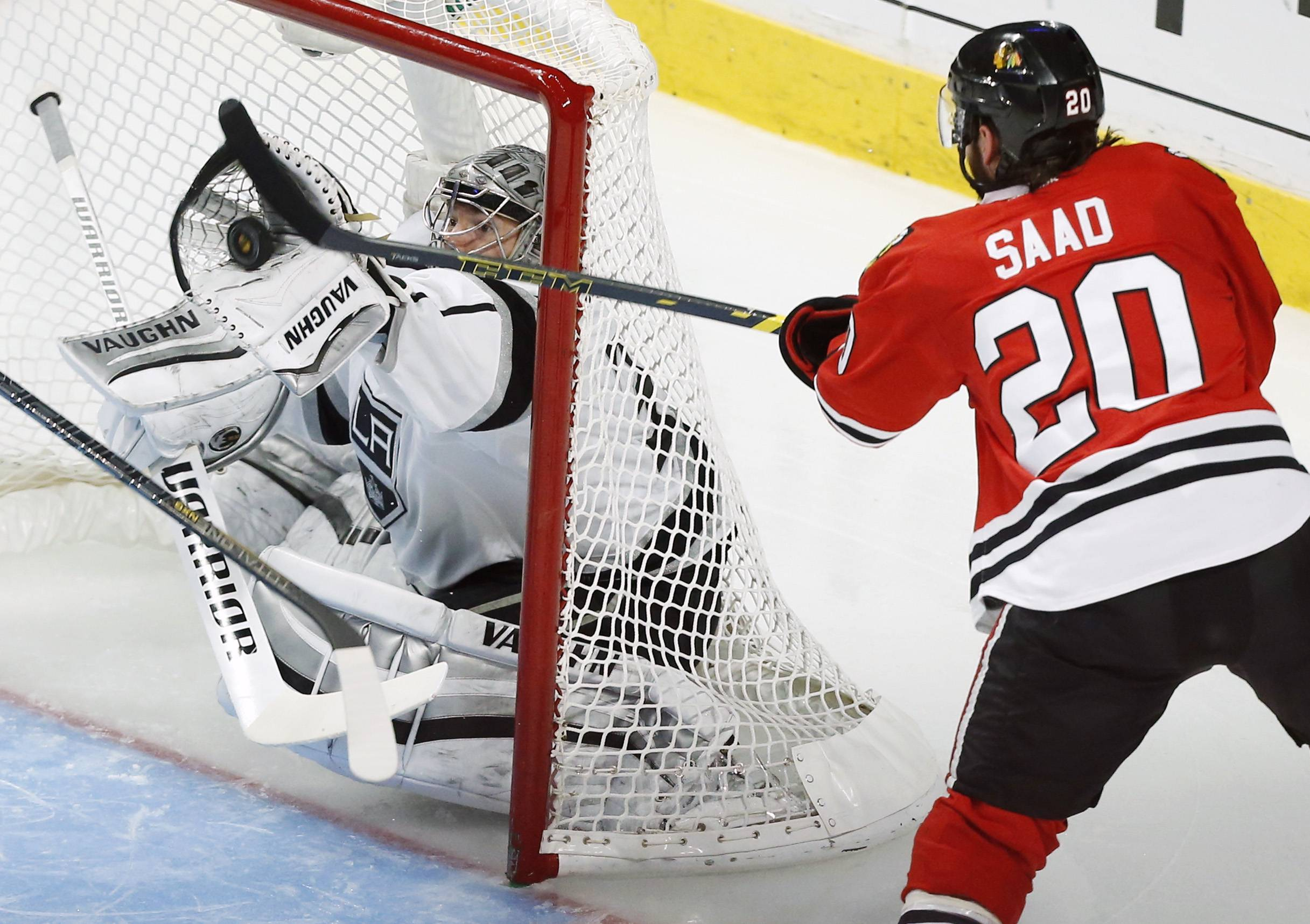 Los Angeles Kings goalie Jonathan Quick, left, saves a goal shot by Chicago Blackhawks left wing Brandon Saad (20) during the second period.