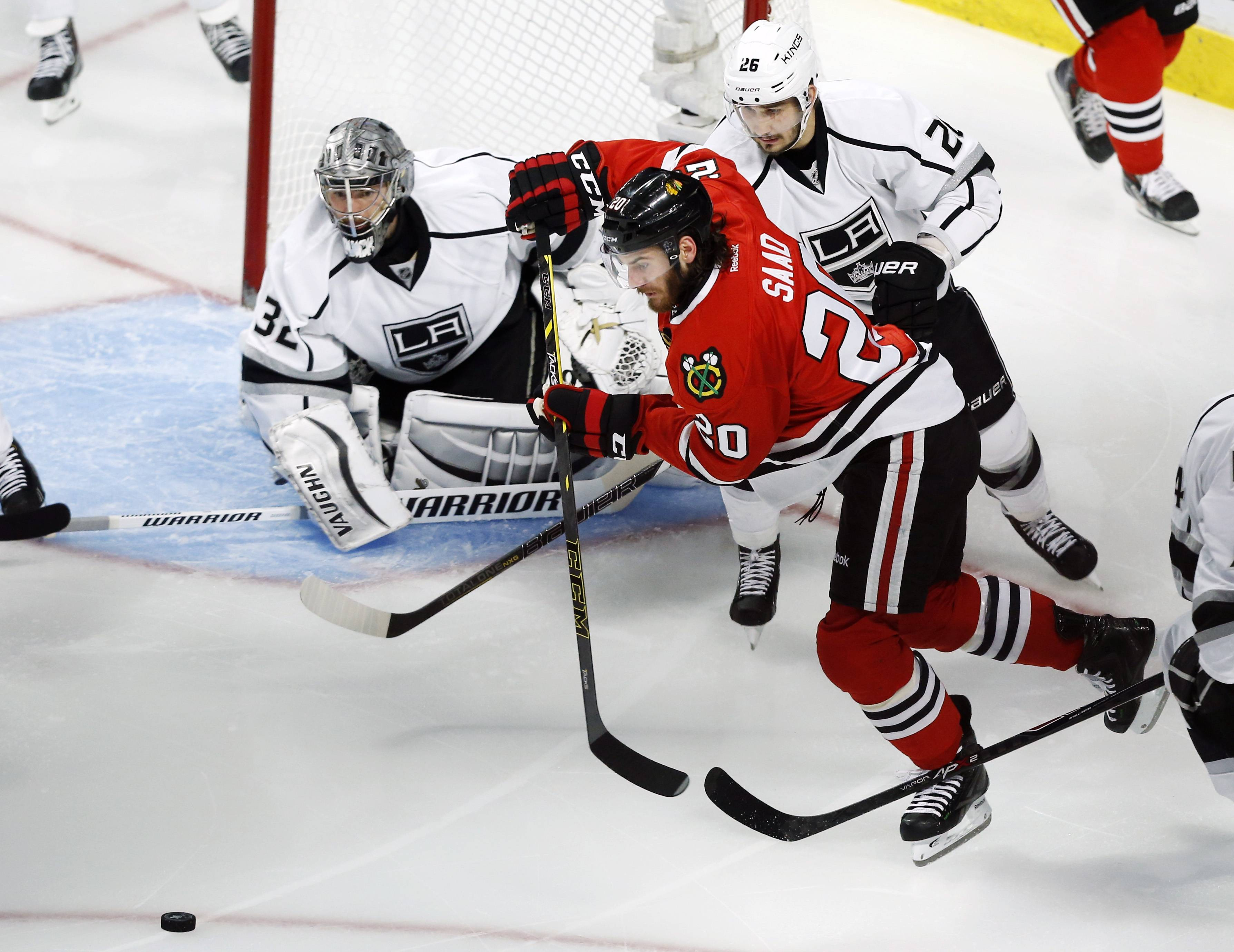 Chicago Blackhawks left wing Brandon Saad (20) goes after the puck against Los Angeles Kings defenseman Slava Voynov (26) during the second period.