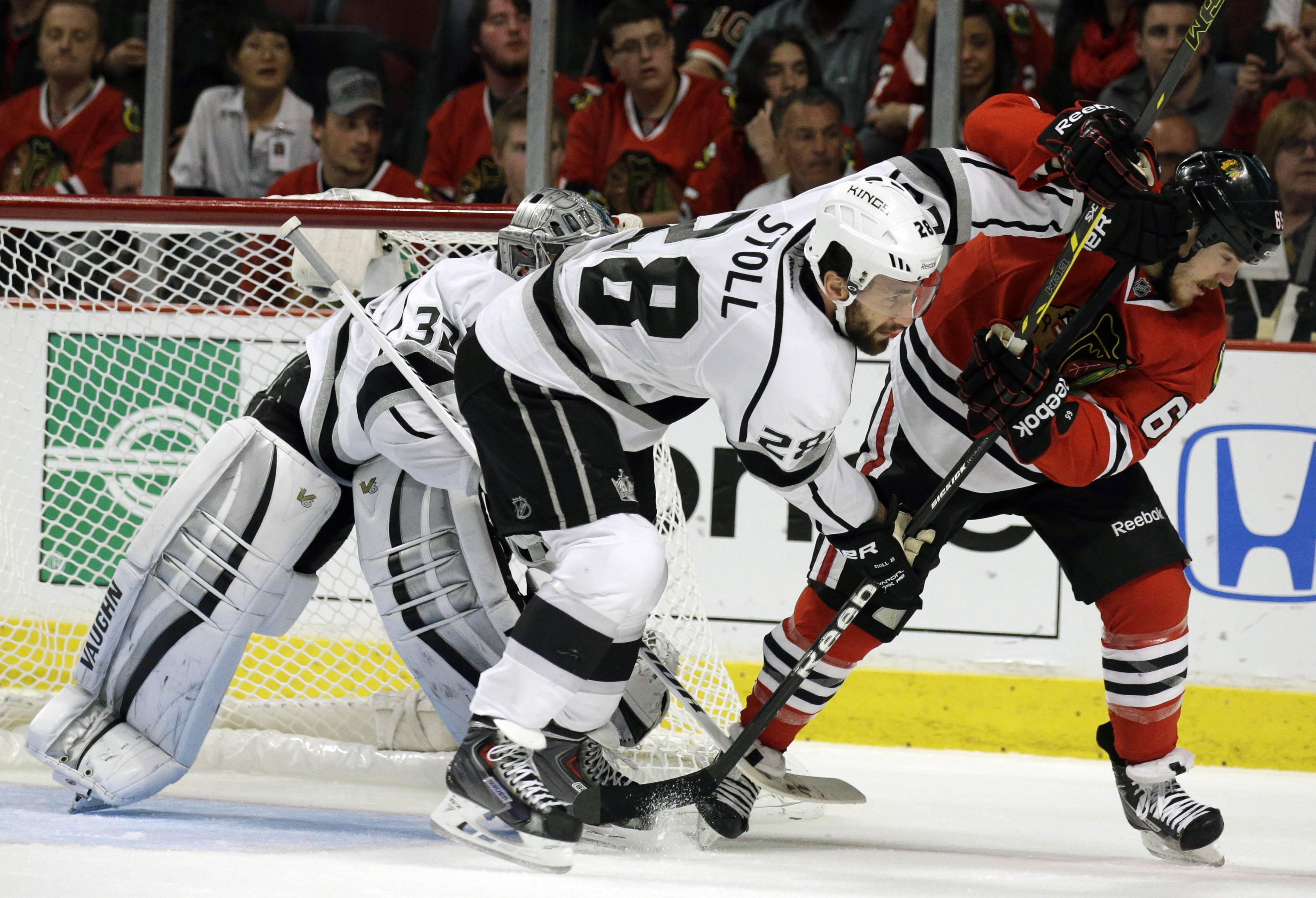 Los Angeles Kings center Jarret Stoll (28) and Chicago Blackhawks center Andrew Shaw (65) battle for a position as they wait for the puck during the second period.