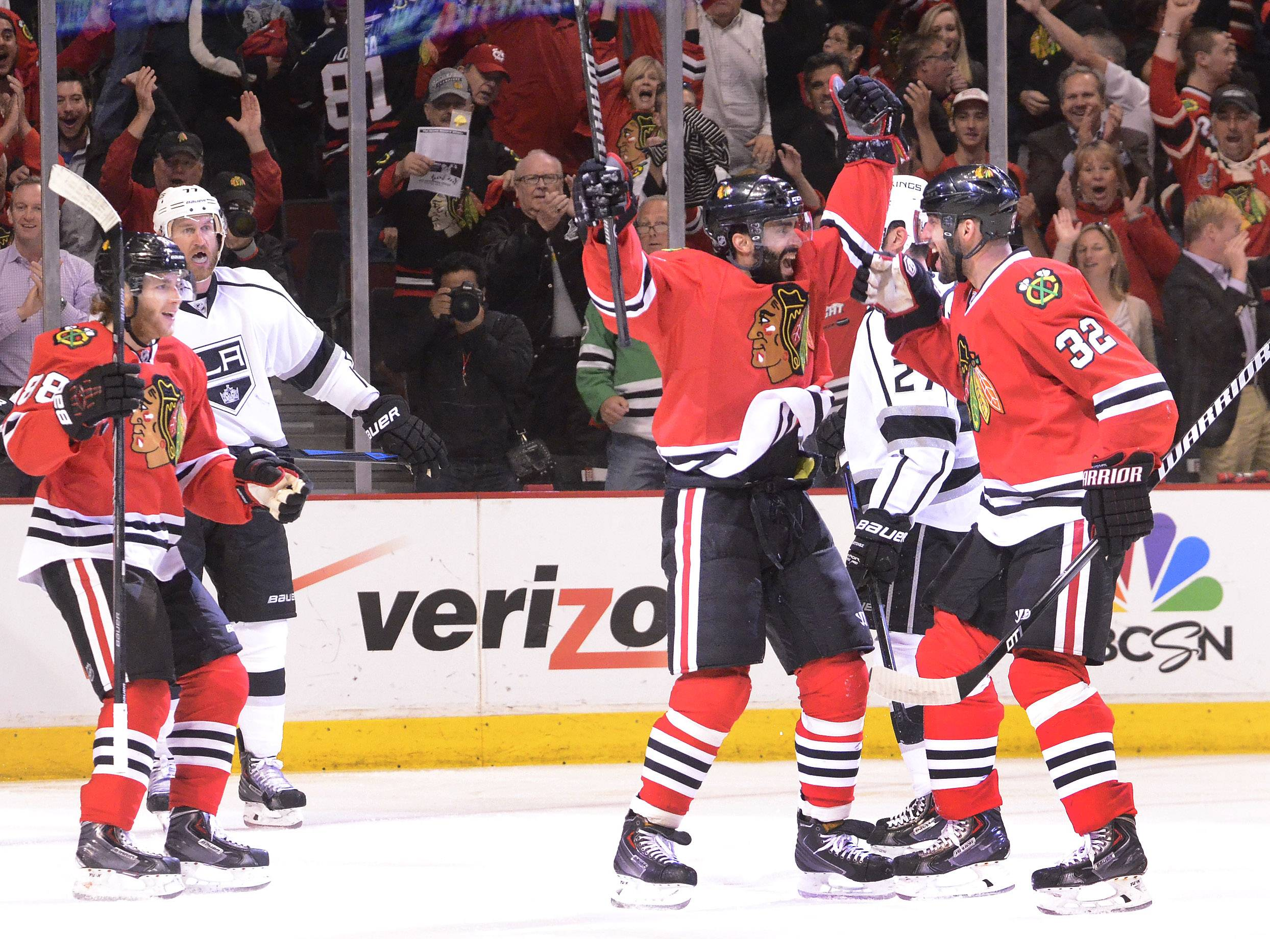 Chicago Blackhawks defenseman Johnny Oduya, center, celebrates his first-period goal with Chicago Blackhawks right wing Patrick Kane, left and Chicago Blackhawks defenseman Michal Rozsival.