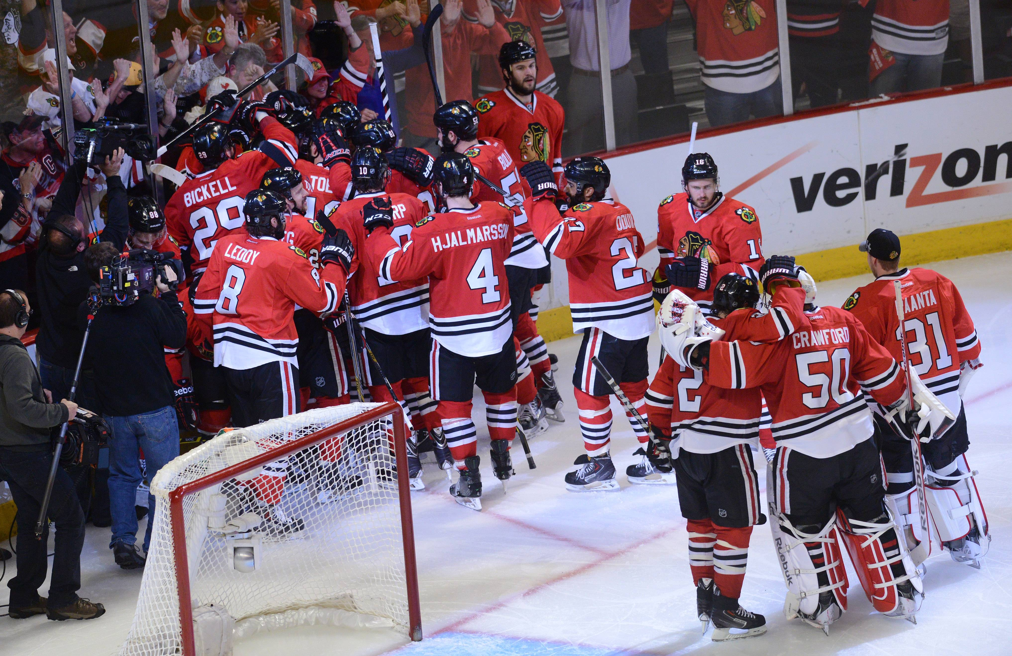Chicago Blackhawks center Michal Handzus is mobbed after scoring game winner.