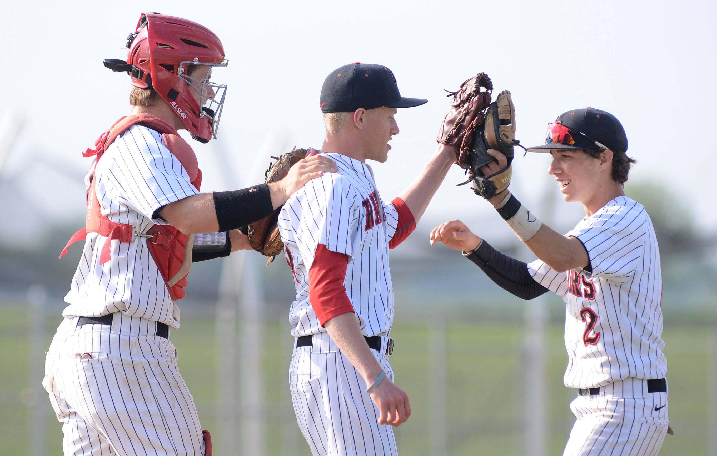Huntley catcher Mark Skonieczny, left, pitcher Eric Luecht, center, and Johnny Nugent celebrate their win over Larkin in the Class 4A regional semifinals at DeKalb High School on Wednesday.
