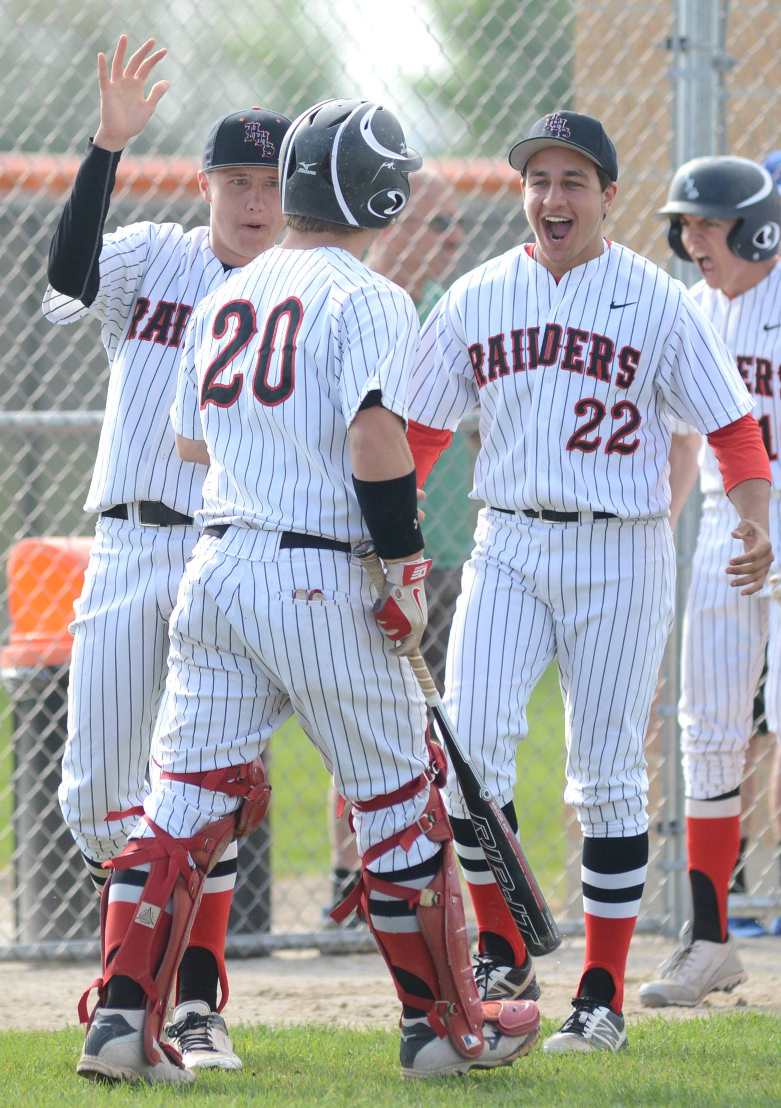 Huntley's Johnny Nugent, left, and Adam Kalish, right, celebrate with Mark Skonieczny after the Red Raiders score in the fifth inning of the Class 4A regional semifinals vs. Larkin at DeKalb High School on Wednesday.