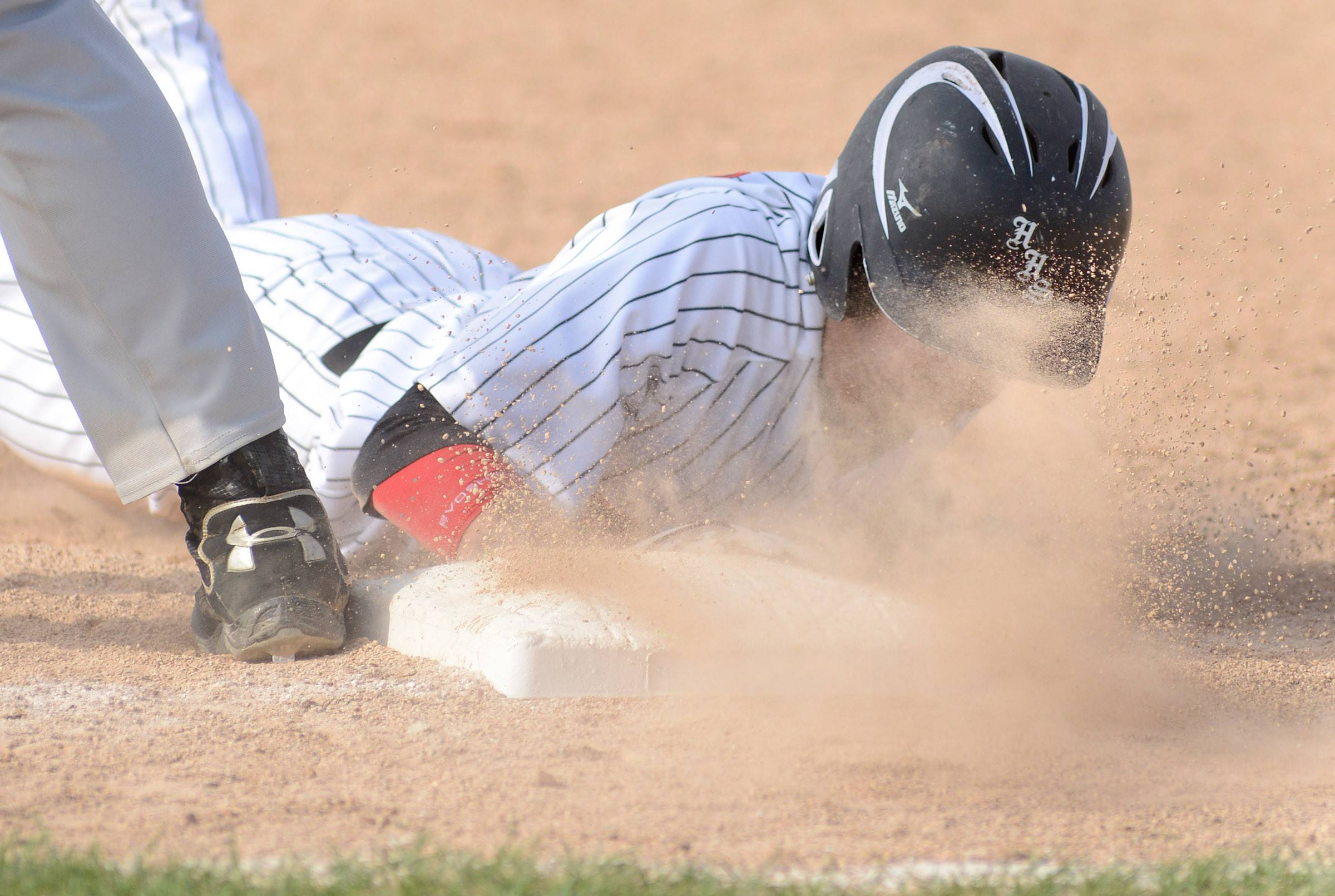 Larkin's Huntley's Dillon DellAquila tastes some dirt as he slides safely back to first base in the fifth inning of the Class 4A regional semifinals at DeKalb High School on Wednesday, May 28. Minutes later he would score a run for the Red Raiders.