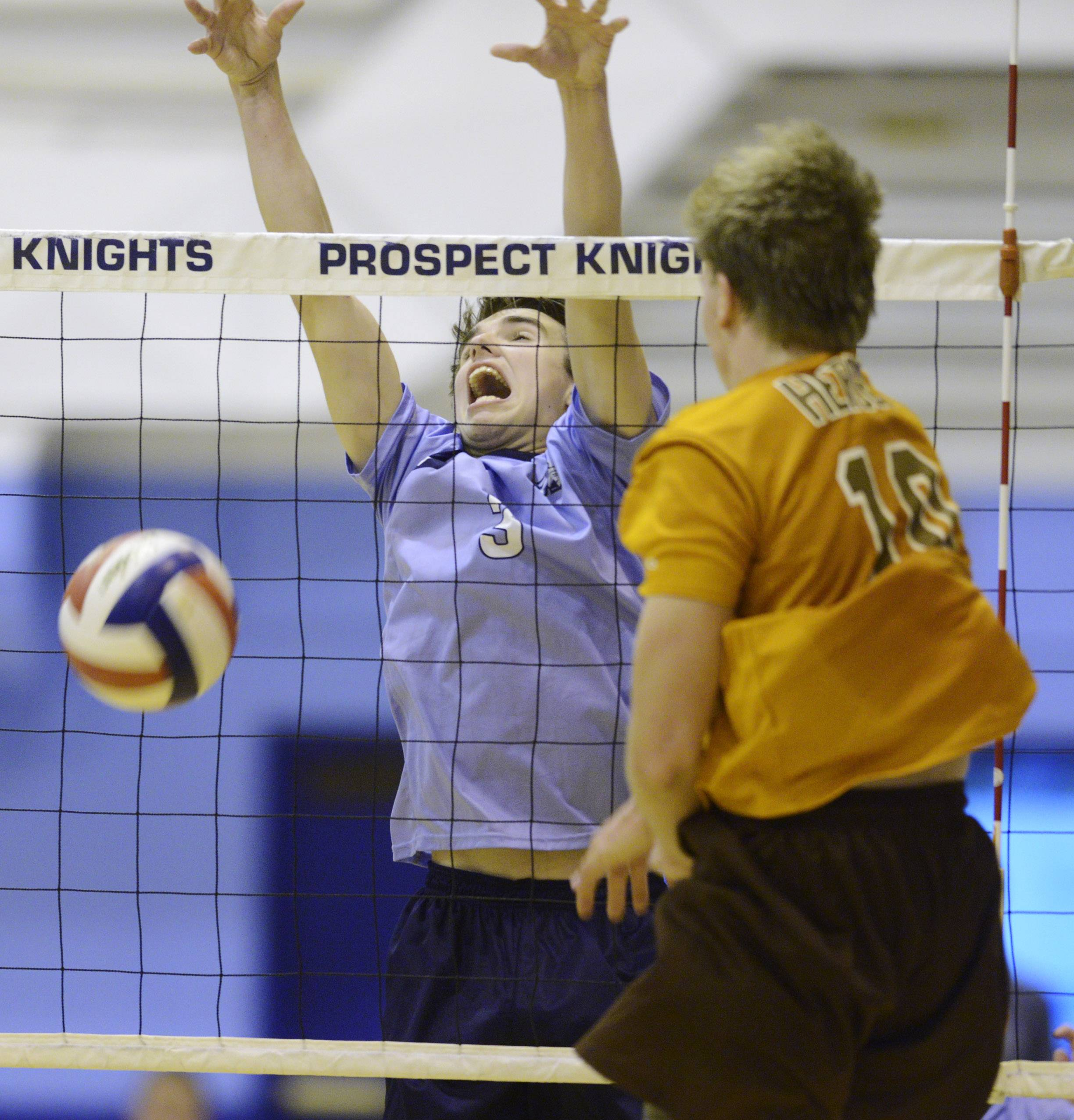 Prospect's Alex Blethen, left, blocks a kill attempt by Hersey's Matt Torvik during Wednesday's regional final in Mount Prospect.
