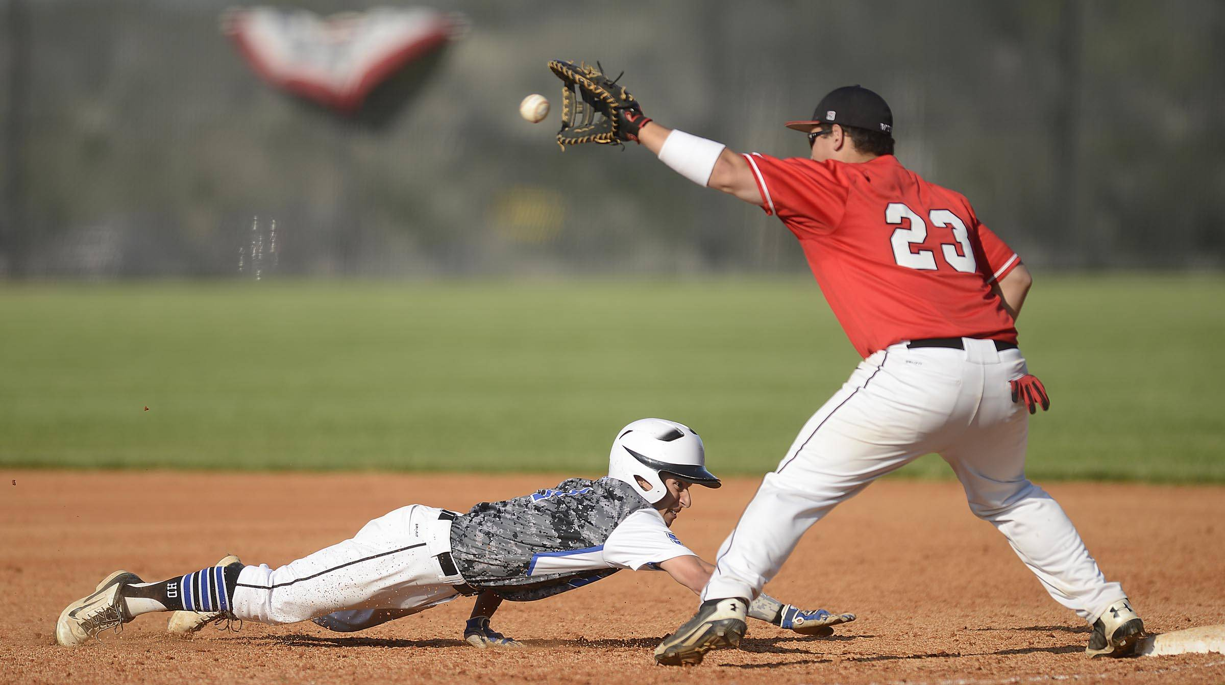St. Charles North's Anthony Lambert dives safely back to first base as Glenbard East's John Allen receives the pick off throw in the regional semifinal game in St. Charles.