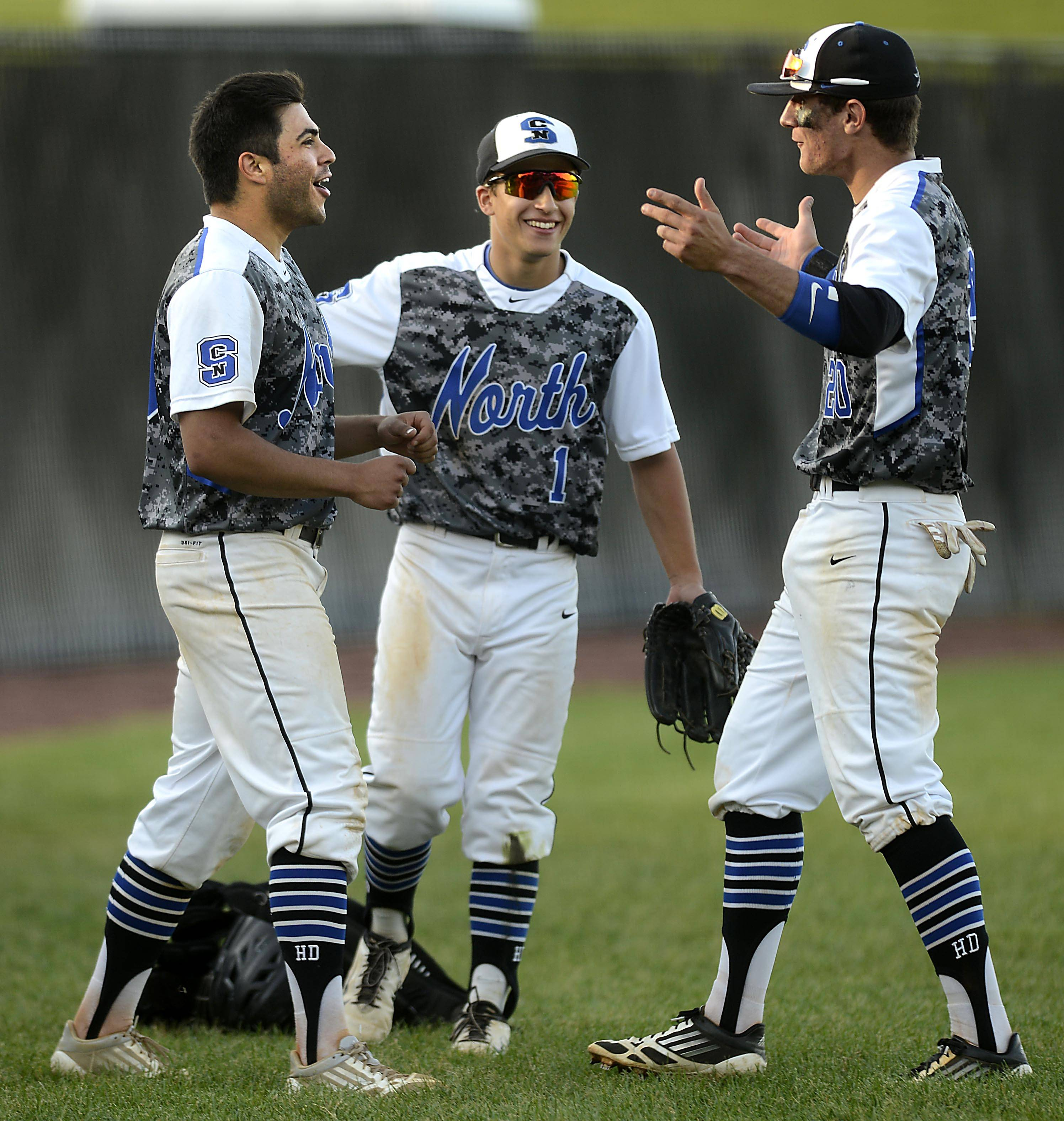 St. Charles North starting pitcher Frankie Farry, left, and teammates Anthony Lambert and Cory Wright, right, celebrate their win against Glenbard East in the regional semifinal game in St. Charles.