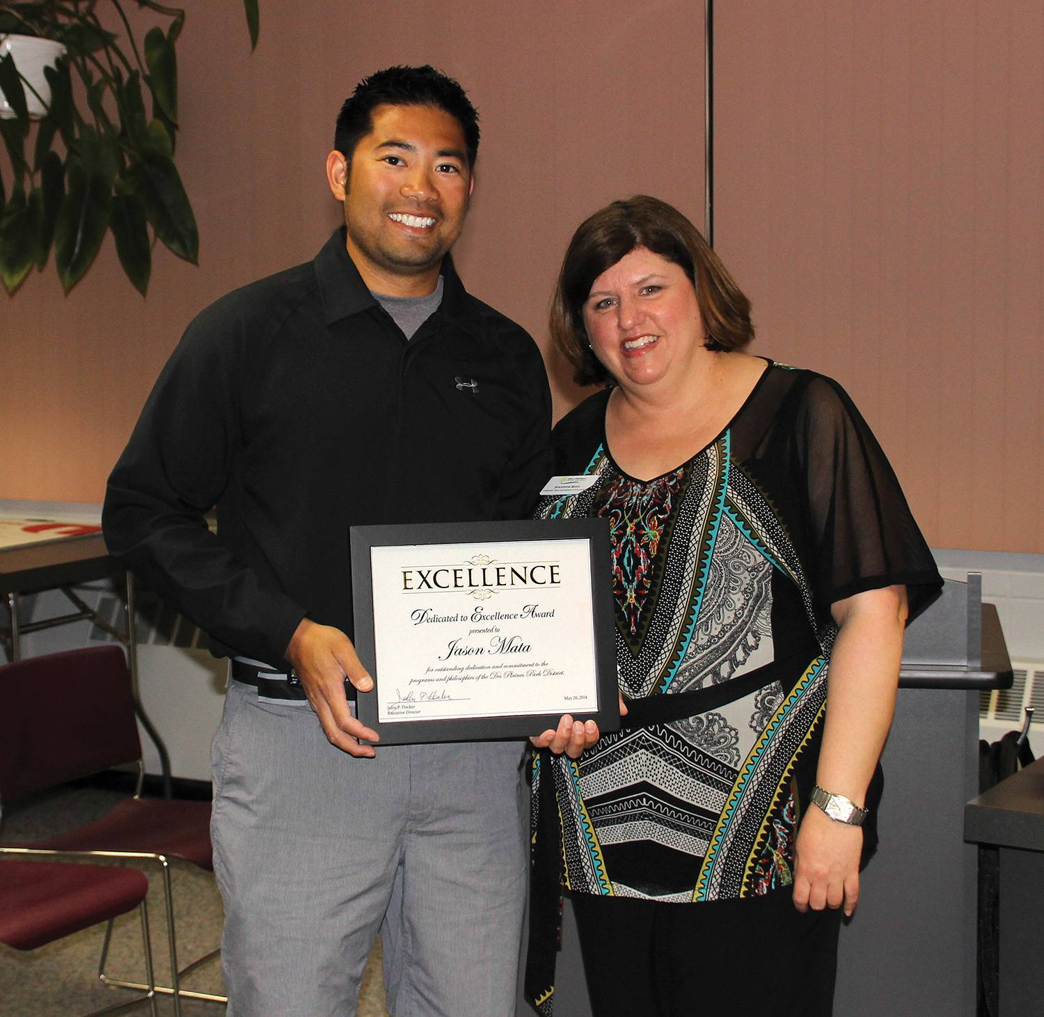 Jason Mata received the Dedicated to Excellence Award at the May 20 Des Plaines Park Board Meeting, from Jennifer Boys, Assistant Superintendent of Recreation.Gene Haring