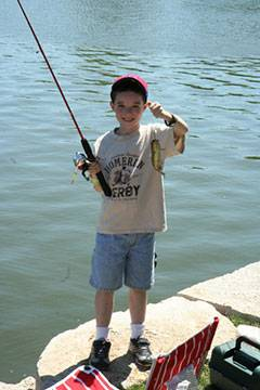 A boy shows off his fish at the annual Father's Day Weekend Fishing Derby.Schaumburg Park District