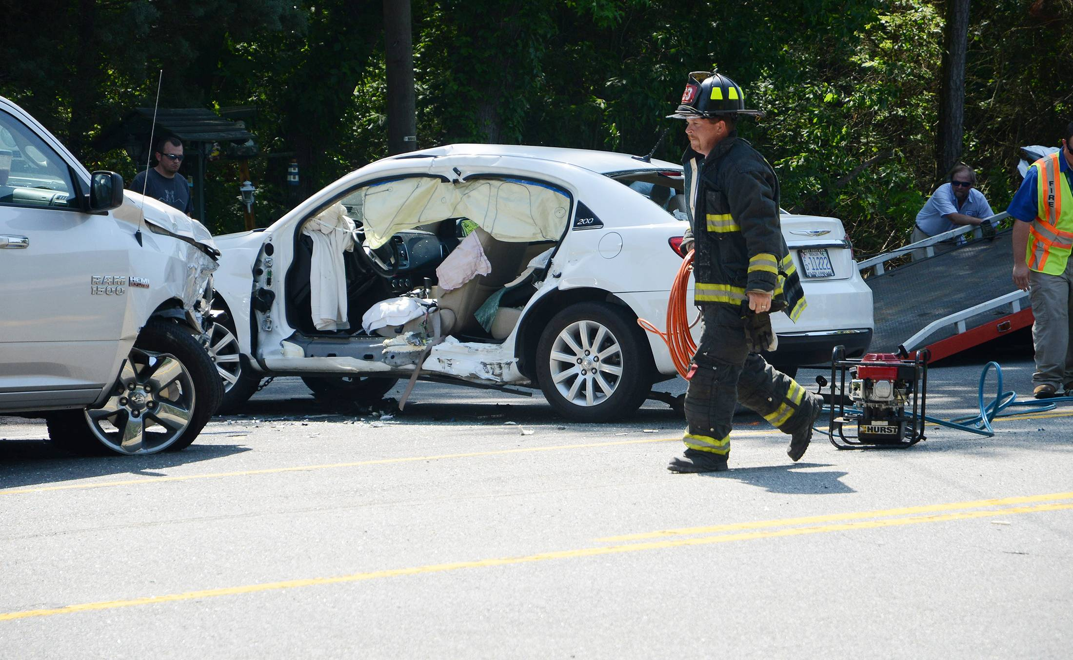 A North Lenoir, N.C. firefighter takes equipment back to the truck after a woman, pinned in her white vehicle, was rescued by the jaws of life, in Kinston, N.C., earlier this month. The economic and societal harm from motor vehicle crashes amounted to a whopping $871 billion in a single year, according to a study released Thursday by the National Highway Traffic Safety Administration.