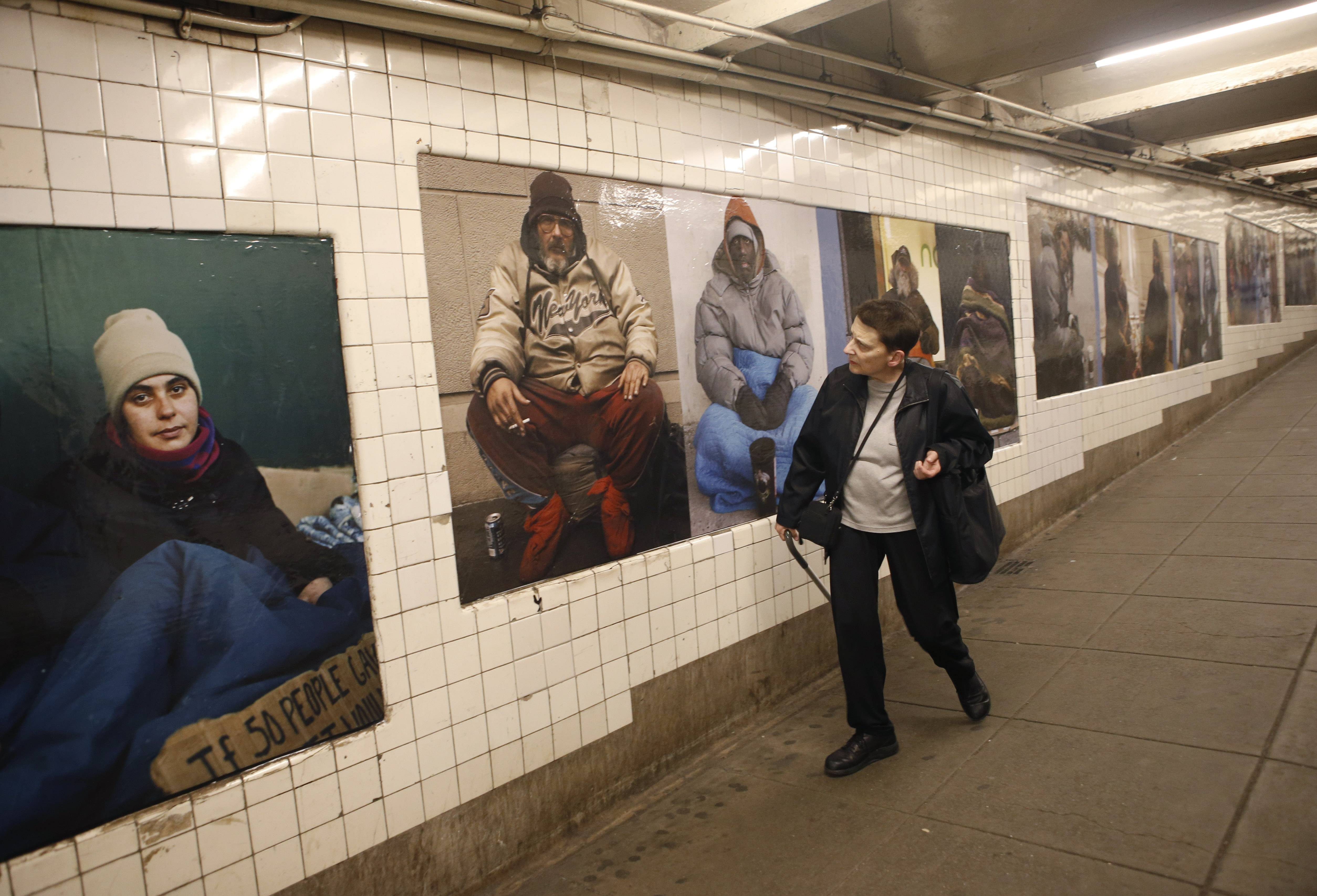 A woman cranes her neck as she passes by some of photographer Andres Serrano's portraits of homeless New Yorkers currently on display at the West 4th Street subway station in New York. Serrano chose to show his portraits in some of the very places his unassuming subjects often populate — a subway station, a park and a church.