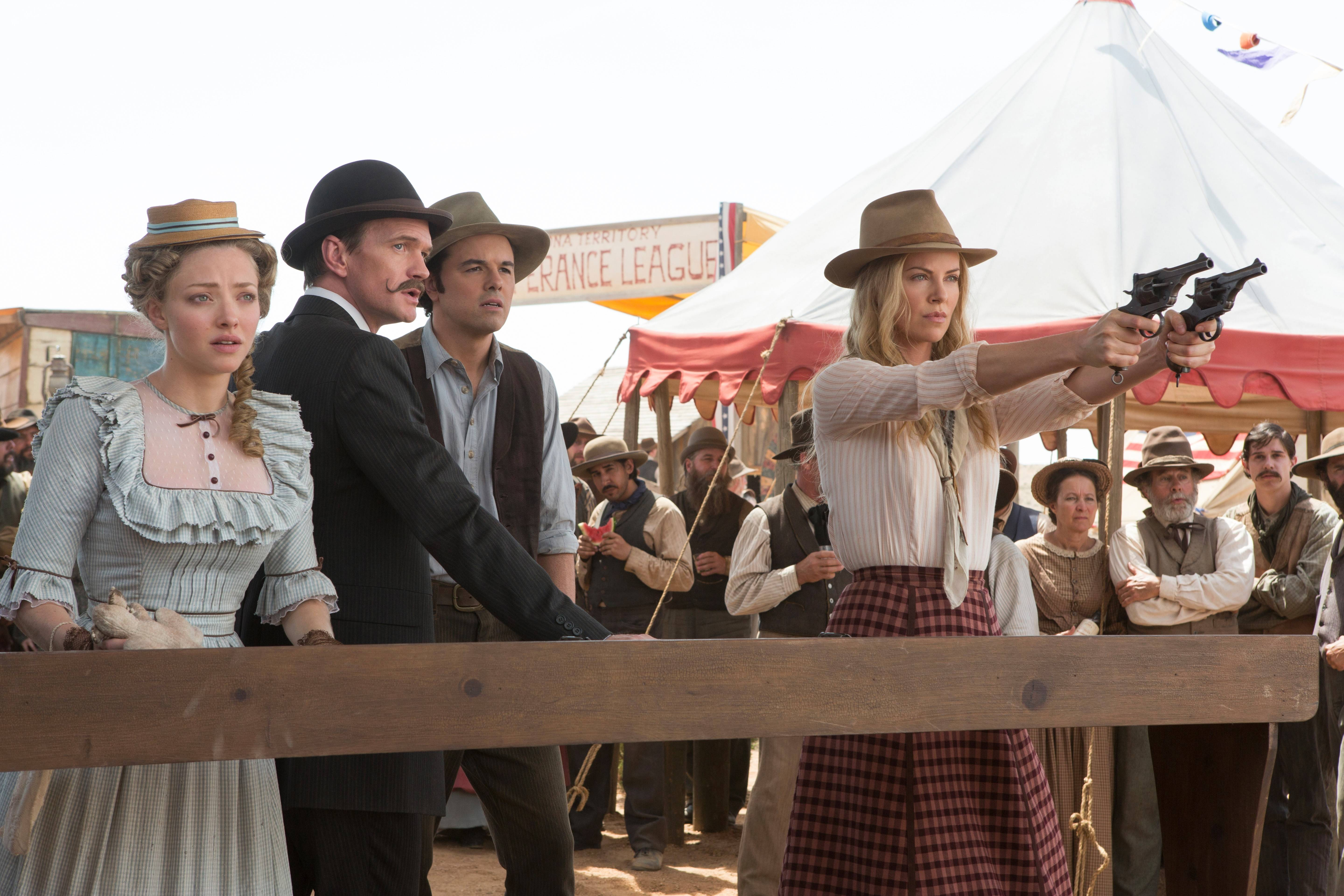"Louise (Amanda Seyfried), left, Foy (Neil Patrick Harris) and Albert (director/producer Seth MacFarlane) watch in awe as Anna (Charlize Theron) handles shootin' irons in ""A Million Ways to Die in the West."""