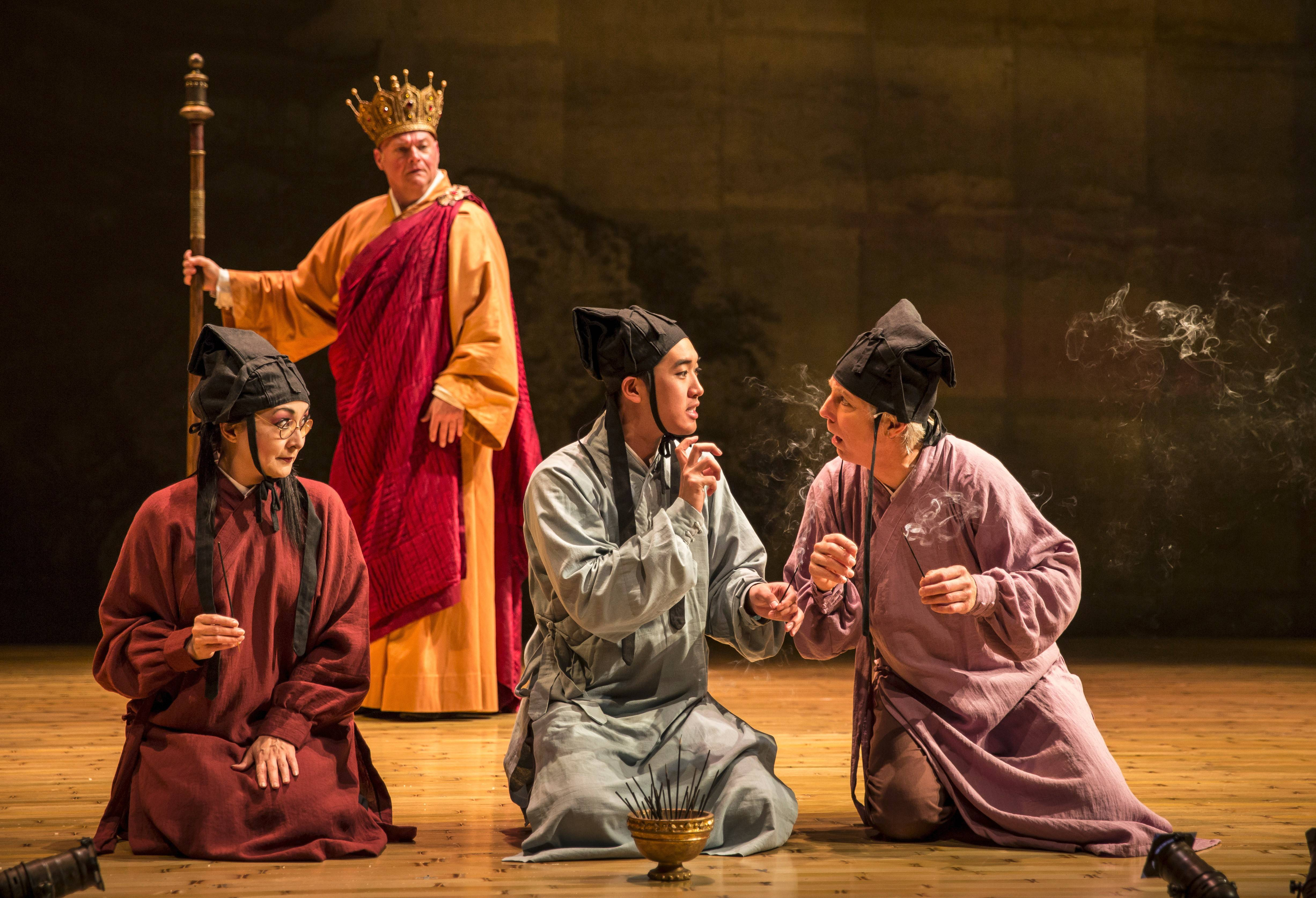 "Monks Lisa Tejero, left, Vin Kridakorn and Richard Howard gossip about the White Snake's identity as Fa Hai (Matt DeCaro), background, eavesdrops in director Mary Zimmerman's production of ""The White Snake"" at Goodman Theatre in Chicago."