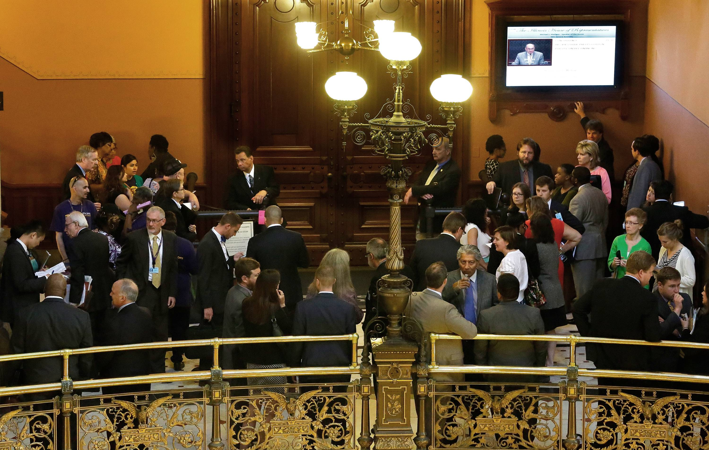 "Lobbyists and lawmakers gather along the ""brass rail"" outside the House chamber during Thursday's session at the Illinois State Capitol in Springfield."