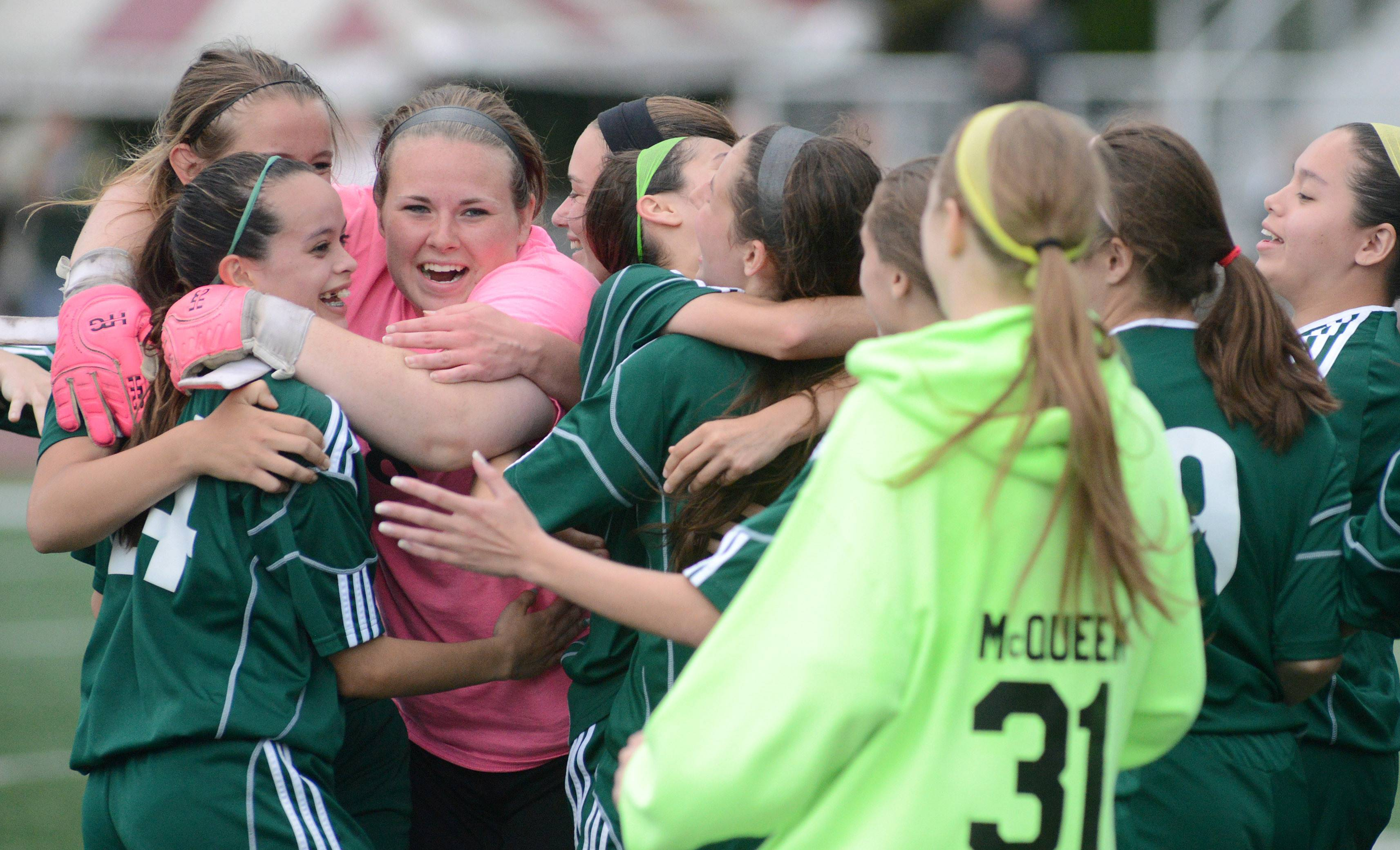 St. Edward goalie Paige Dykstra, facing, in pink, is swarmed by teammates as they rush the field after their Class 1A supersectional win over Chicago Latin at Concordia University in River Forest on Tuesday. St. Edward will take on Manteno in a state semifinal at North Central College in Naperville on Friday at 7 p.m.
