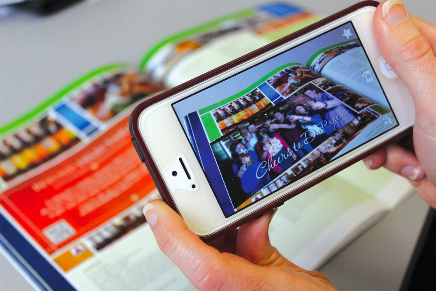 A video plays on a smartphone while the magazine is on the desk. You can see where the video plays over the orange area on the printed guide, while the photos of bottles and other images remain idle.