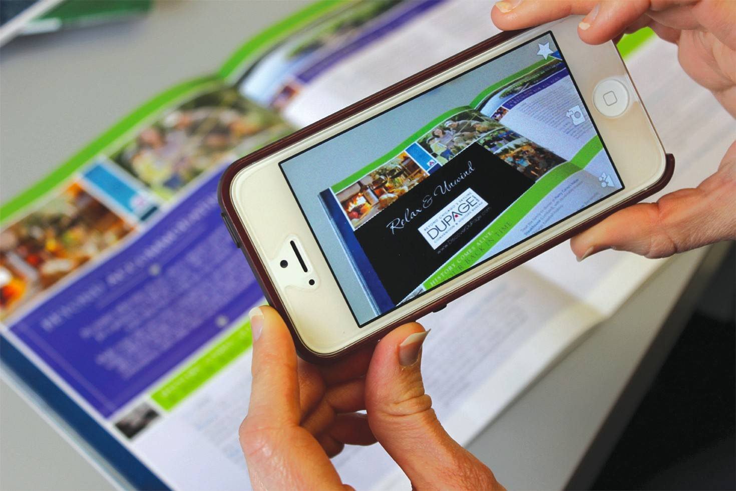 This shows a video playing on a smartphone while the printed guide is on the desk. The video is playing over the purple area on the printed guide, while the other images remain idle. This is the augmented reality portion of the app.