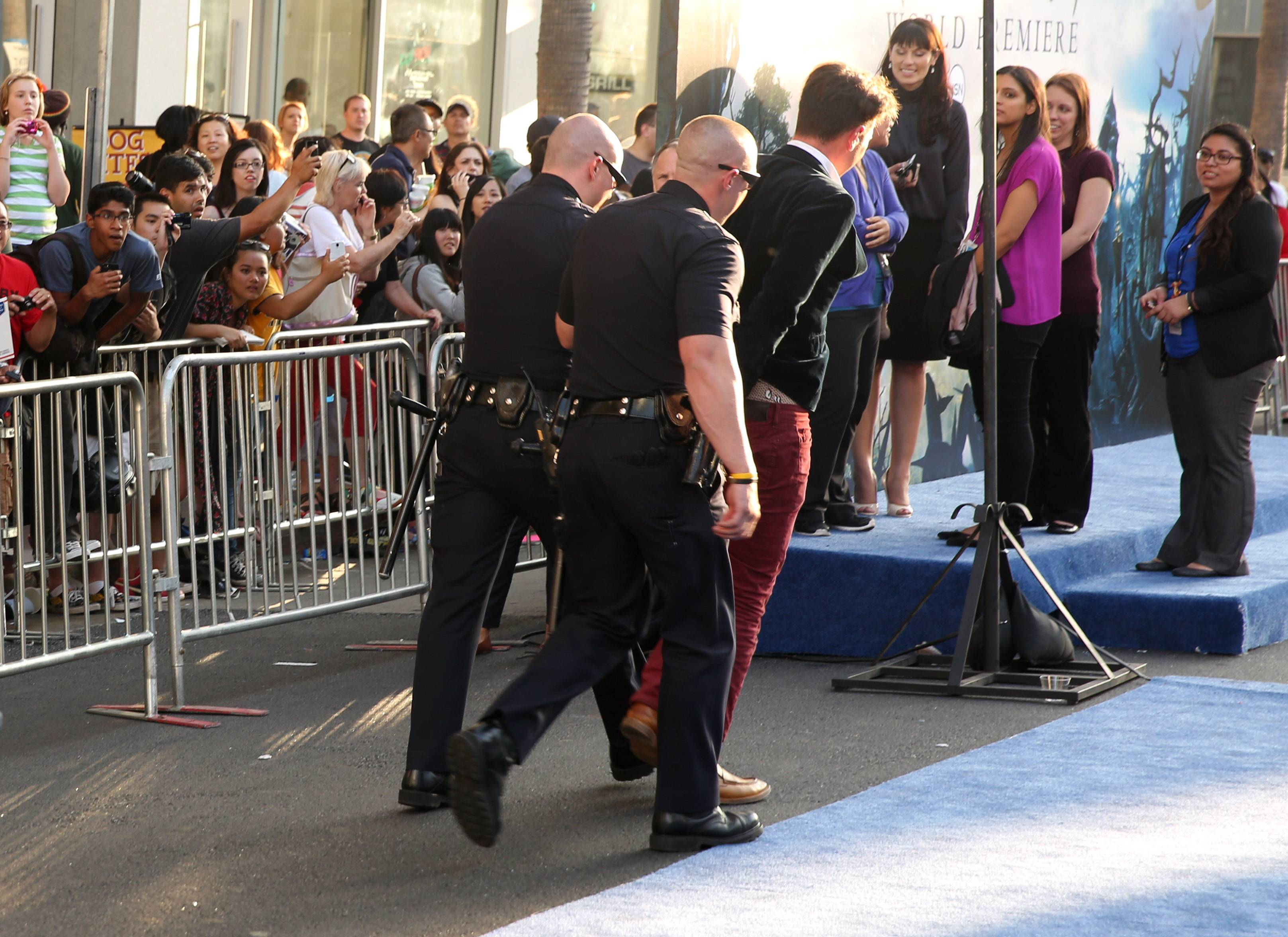 "A fan is walked off carpet in handcuffs after police say he attacked Brad Pitt at the world premiere of ""Maleficent"" at the El Capitan Theatre on Wednesday in Los Angeles."