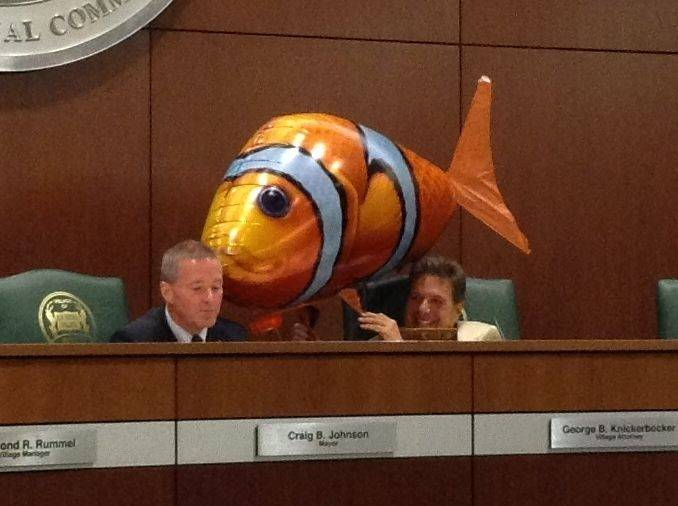 Elk Grove Village Mayor Craig Johnson, left, reads a note from TV personality Svengoolie, delivered by a balloon fish held by Village Attorney George Knickerbocker, right, at this week's village board meeting.