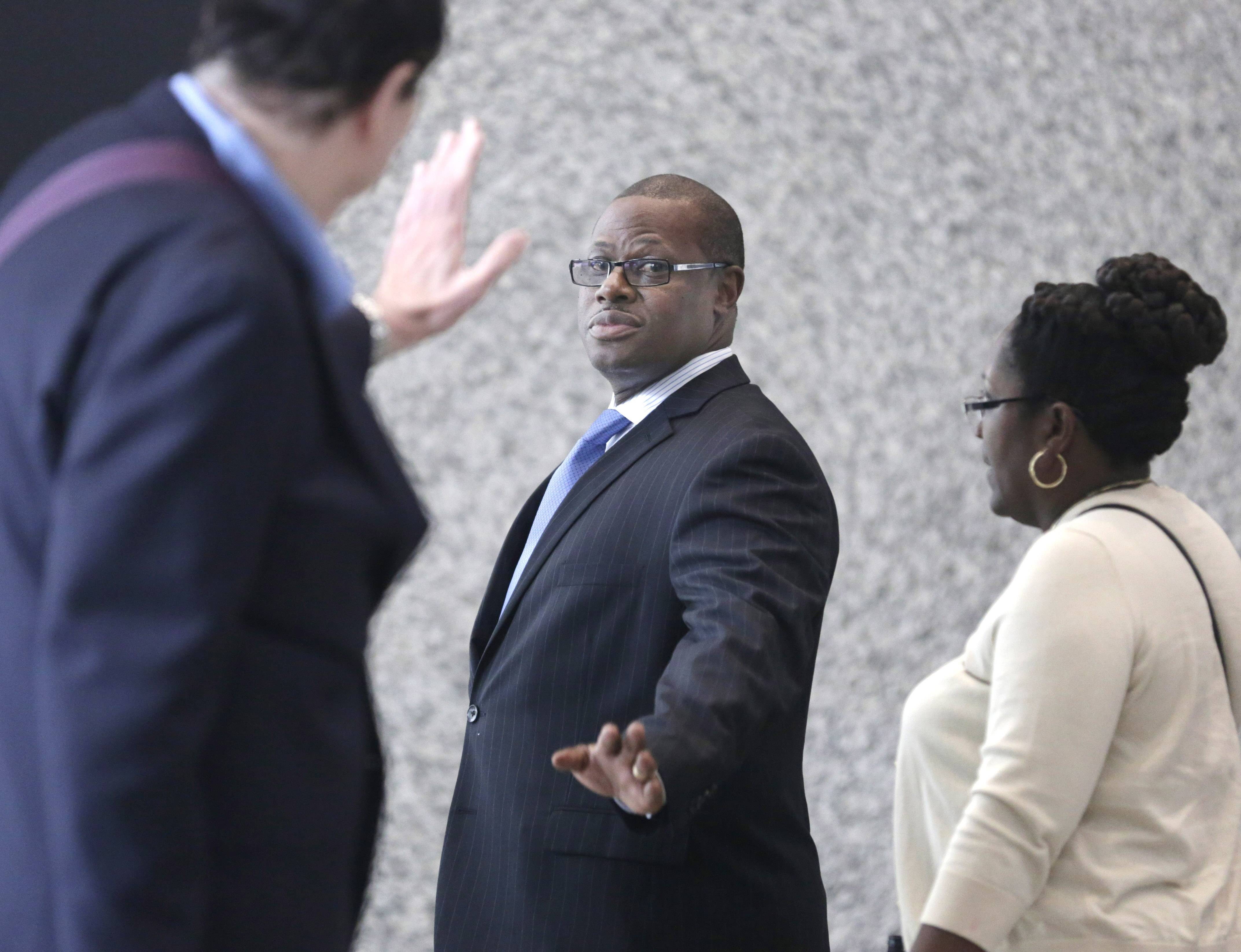State Rep. Derrick Smith, center, waves as he enters federal court for the beginning of jury selection in his corruption trial Wednesday in Chicago. The Chicago Democrat has been charged with accepting a $7,000 bribe in exchange for using his influence to obtain a state grant for a day care center.