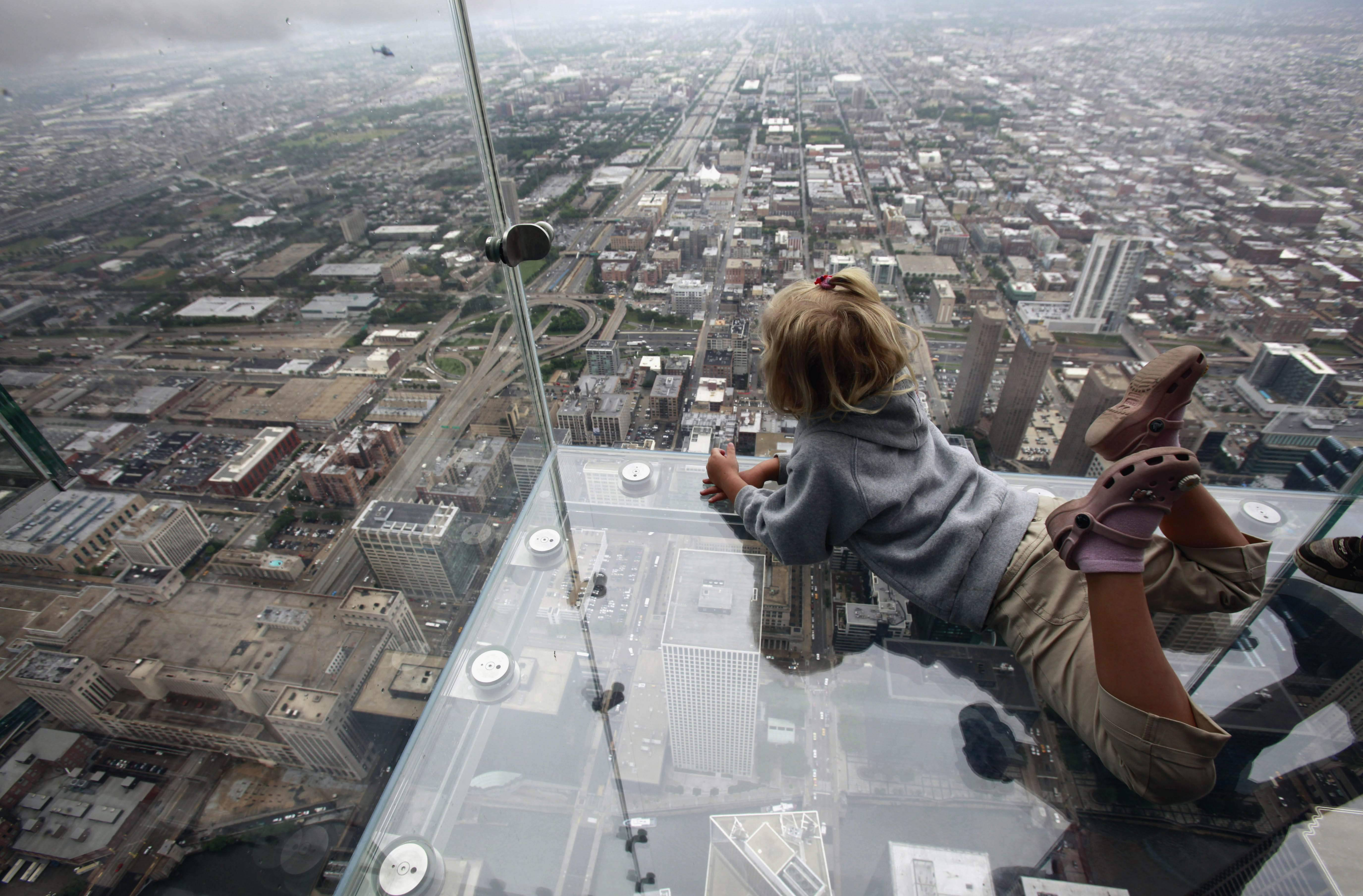 "Anna Kane looks down from the ""The Ledge"" at Chicago's Willis Tower. The see-through glass bays extend about four feet from the building, which was once called the Sears Tower."