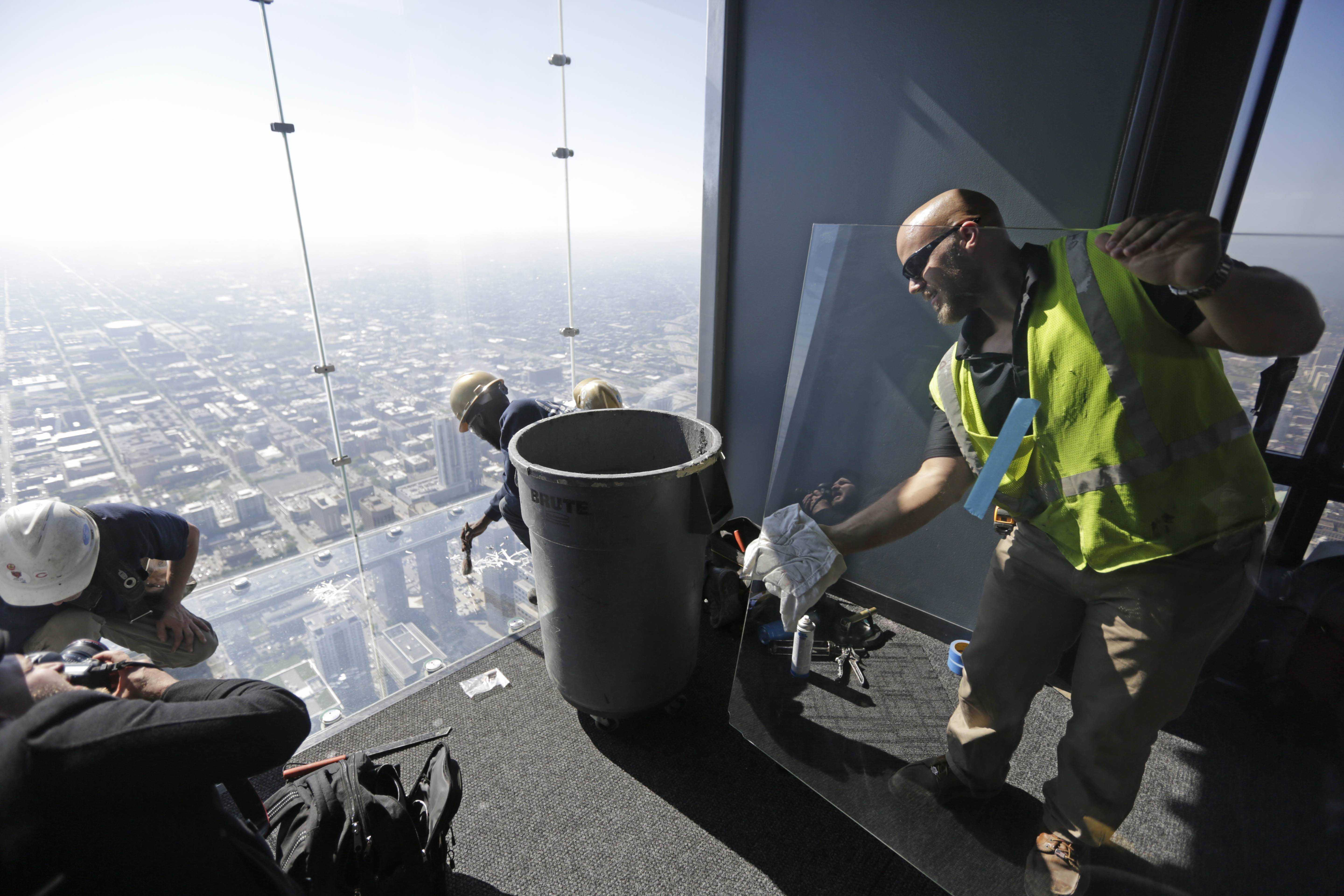 Glaziers from MTH Industries prepare Thursday to replace a layer of protective coating on the floor a transparent ledge that juts out from the 103rd floor of the Willis Tower in Chicago.