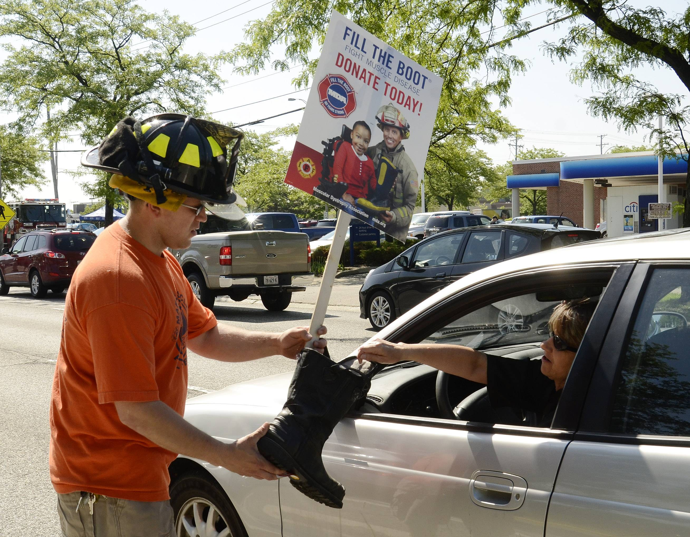Jason Kedrock gets a donation from Debbie Chuk of Palatine during the Arlington Heights firefighters Fill the Boot campaign Friday at the intersection of Palatine Road and Arlington Heights Roads.