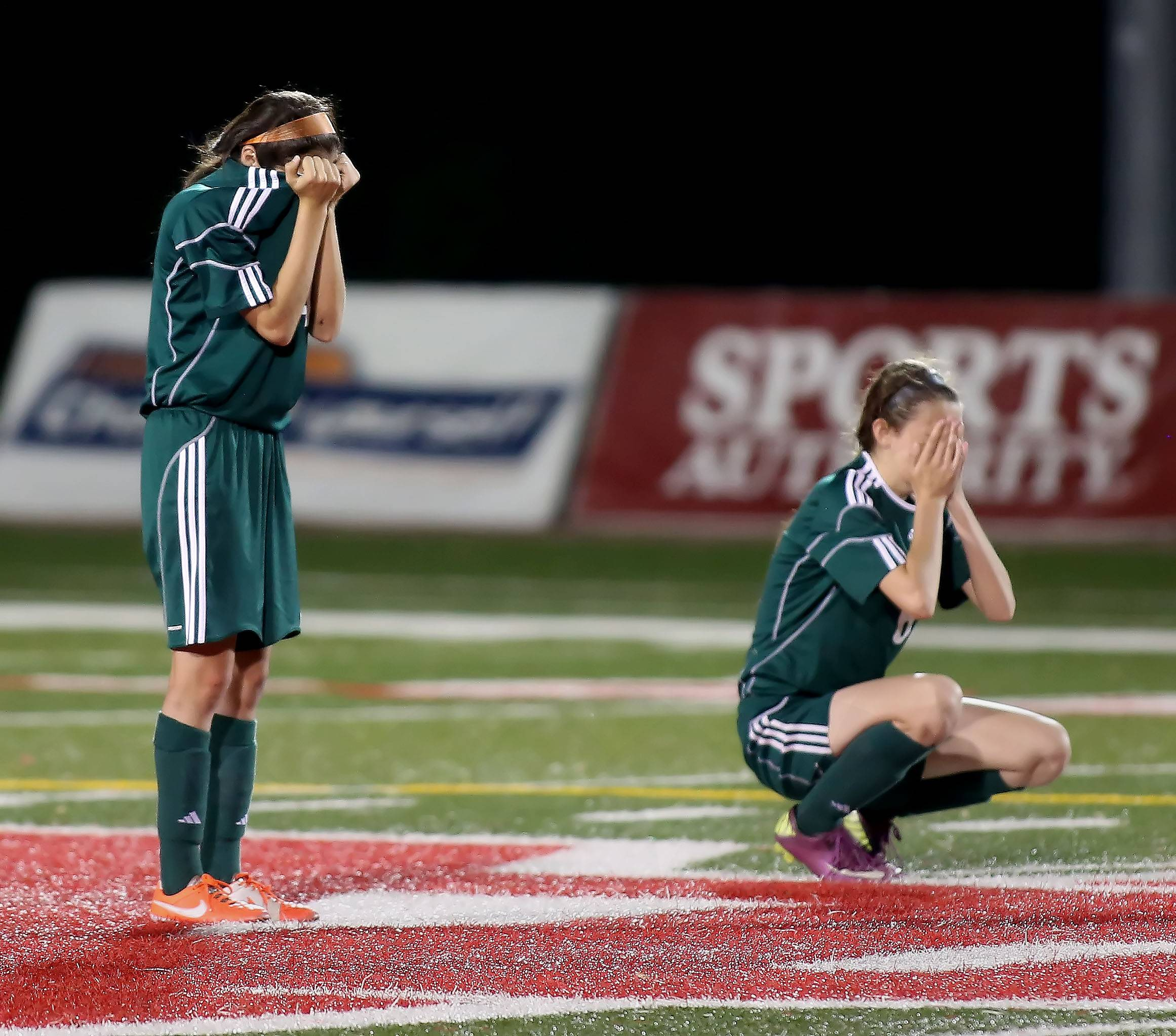 St. Edward's Monica Ramirez, left and Chelsea Gnan react to their loss to Manteno in overtime during the Class 1A state soccer semifinals at North Central College in Naperville on Friday.