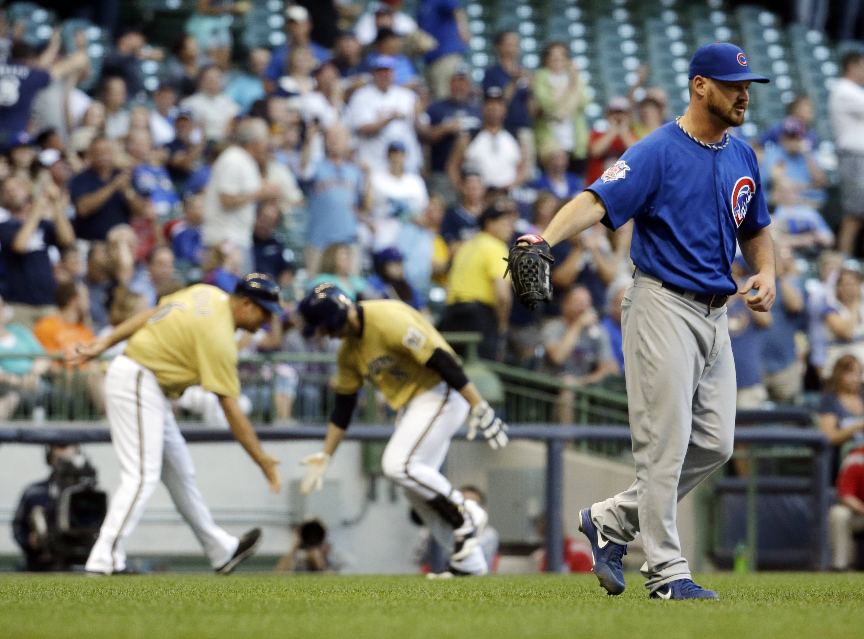 Cubs starting pitcher Travis Wood, right, winces as Milwaukee Brewers' Ryan Braun rounds the bases after Braun hit a two-run home run during the first inning Friday. Wood turned in his shortest outing of the season.