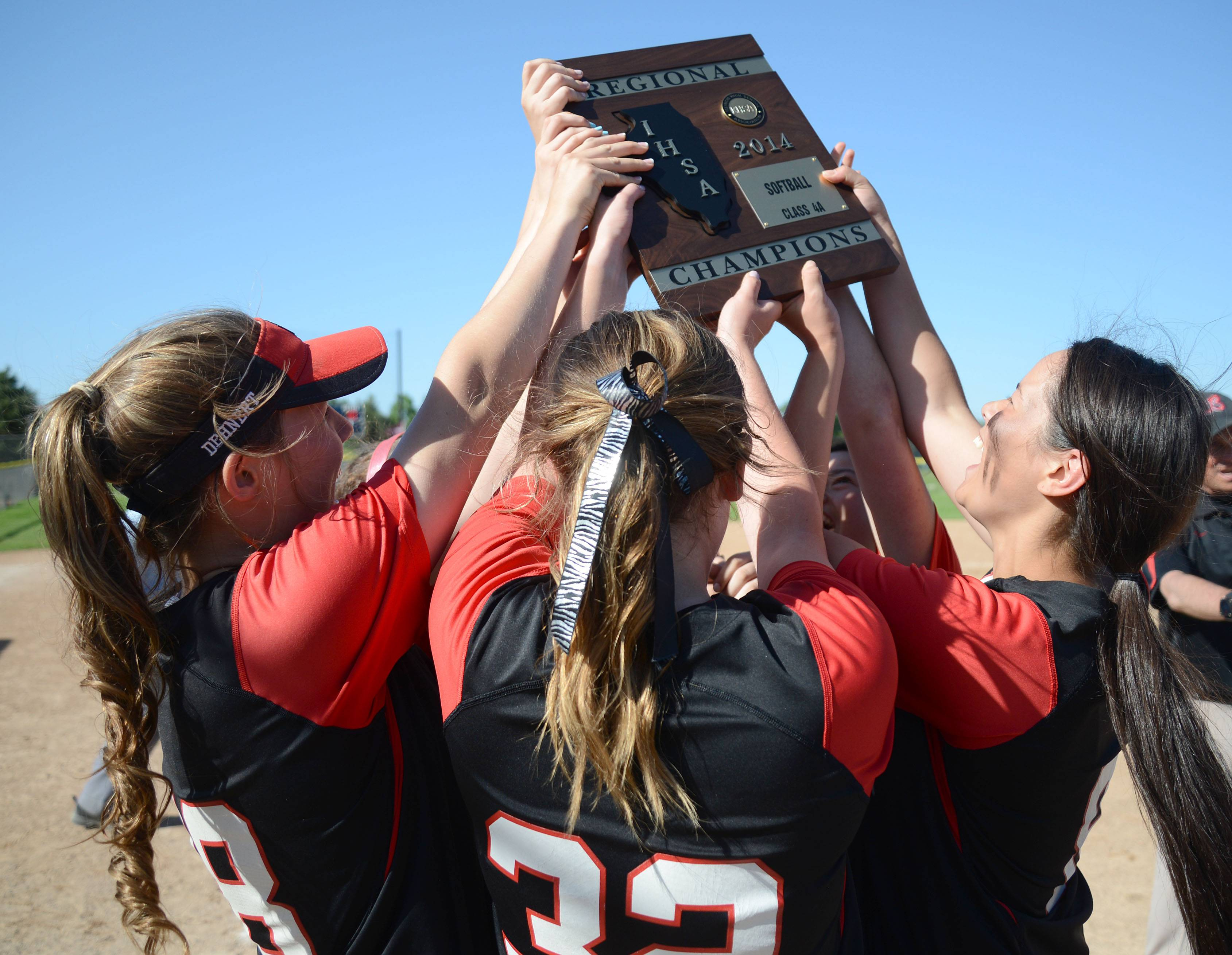 Barrington's Katie Dehnert, left, Carly Kordich, center, and Keenan Dolezal, right, hoist up their Class 4A girls softball regional championship plaque after their 10-0 win over Cary-Grove on Friday.