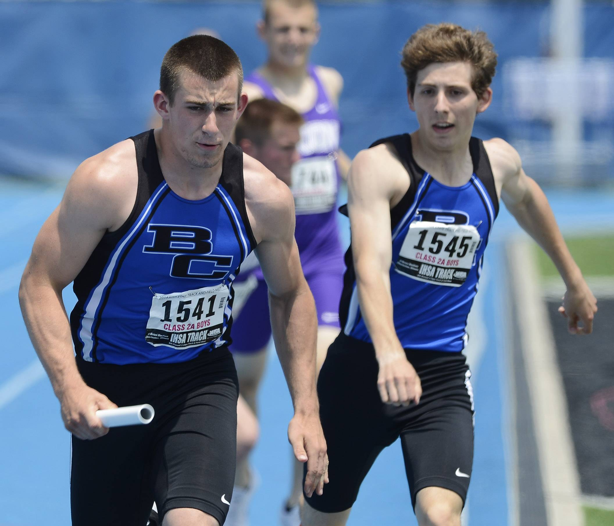 Burlington Central's Casey Matthews, left, runs after taking the baton from teammate Kyle Neubauer in the 4x400-meter relay during the Class 2A boys track and field state preliminaries in Charleston on Friday.