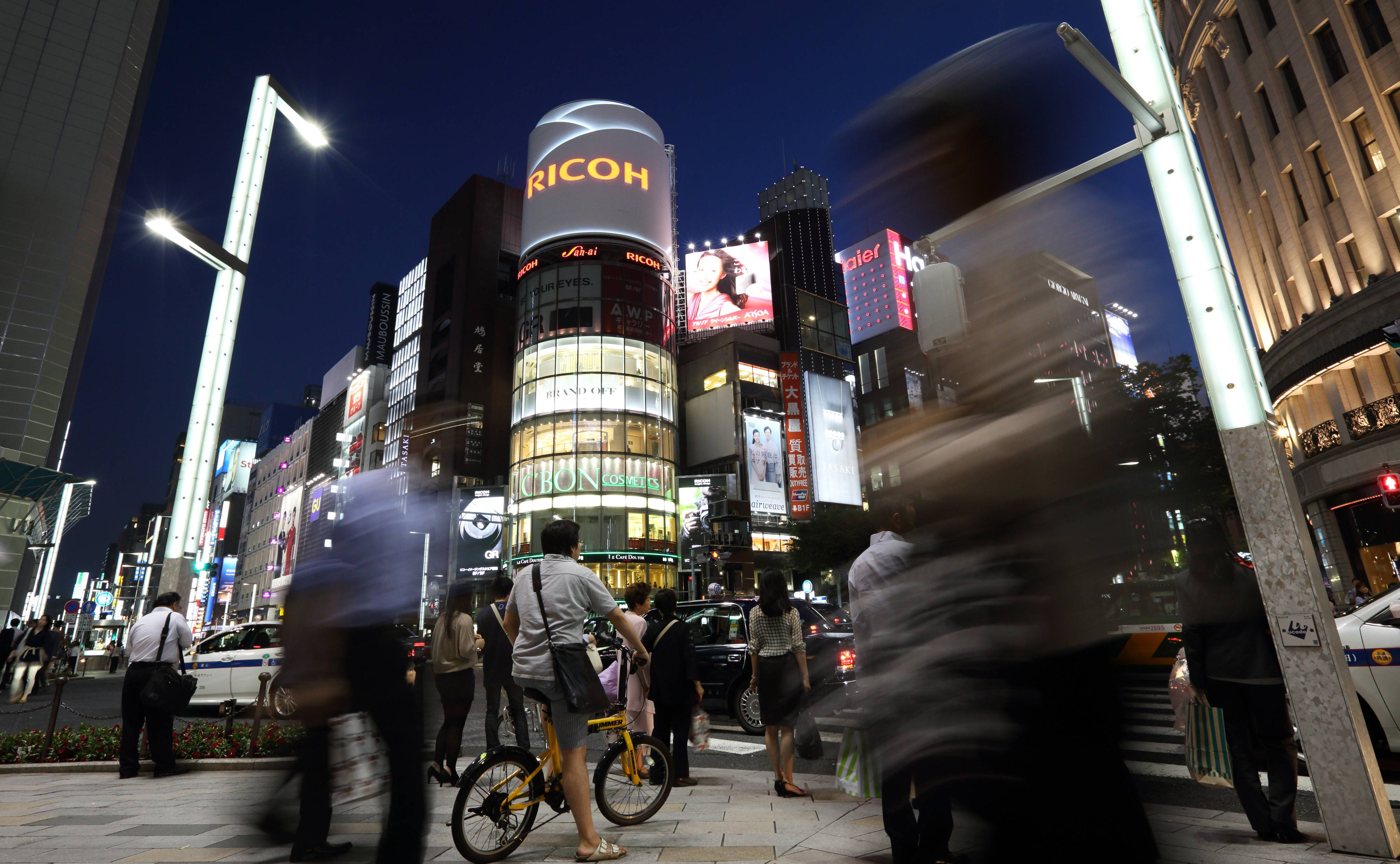Pedestrians and shoppers wait to cross a road at night in the Ginza district of Tokyo, Japan. Japan's consumer prices rose 3.2 percent from a year earlier in April to the highest level since 1991, the government said Friday, largely due to a sales tax increase that is expected to dent growth this quarter.