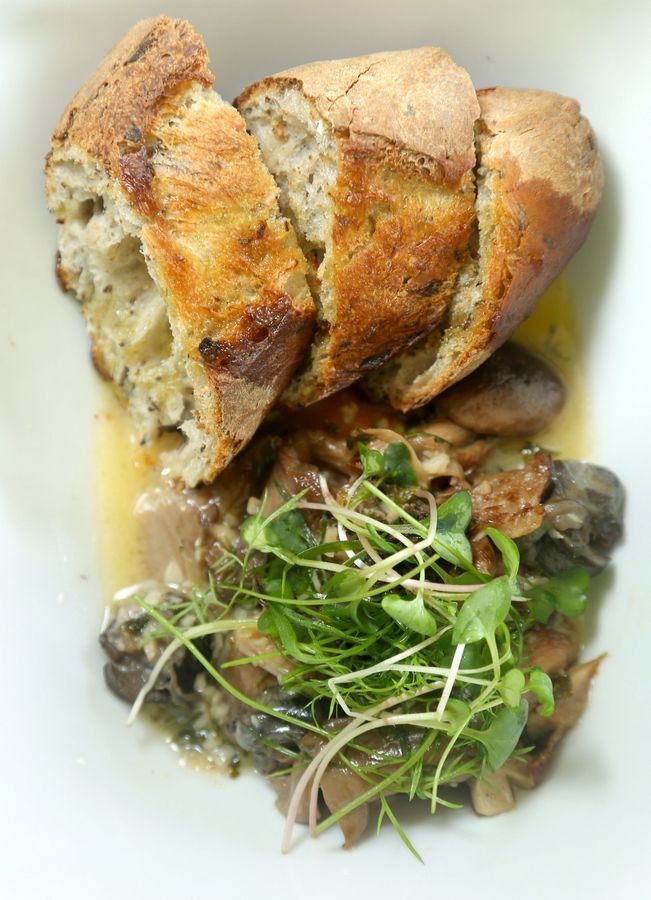 Microgreens and fresh-baked bread accompany burgundy snails at Ad-Lib Geo Cafe in Lindenhurst.