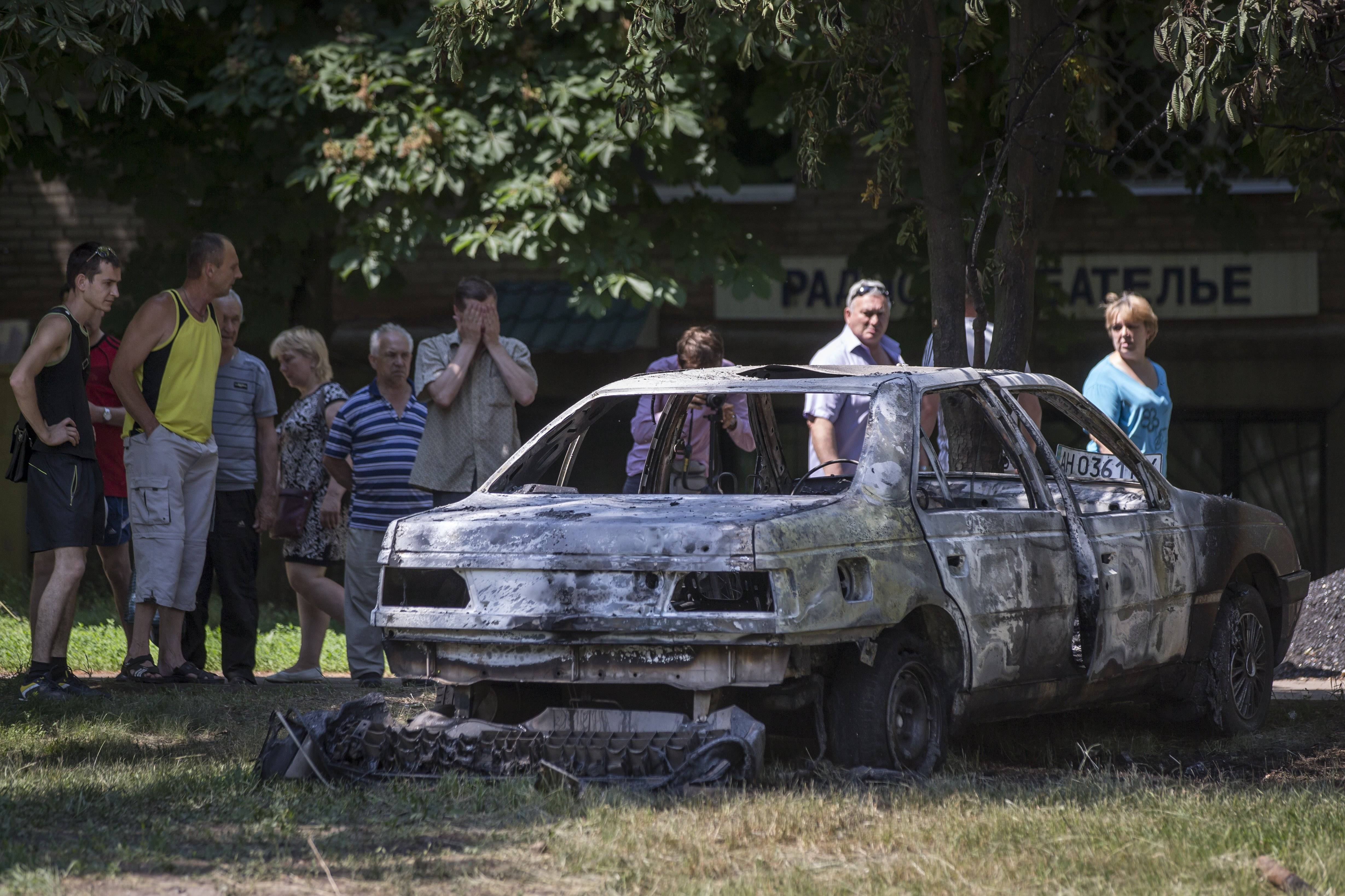 Local people look at a burnt-out car Wednesday following a shelling from Ukrainian government forces, in Slovyansk, Ukraine.