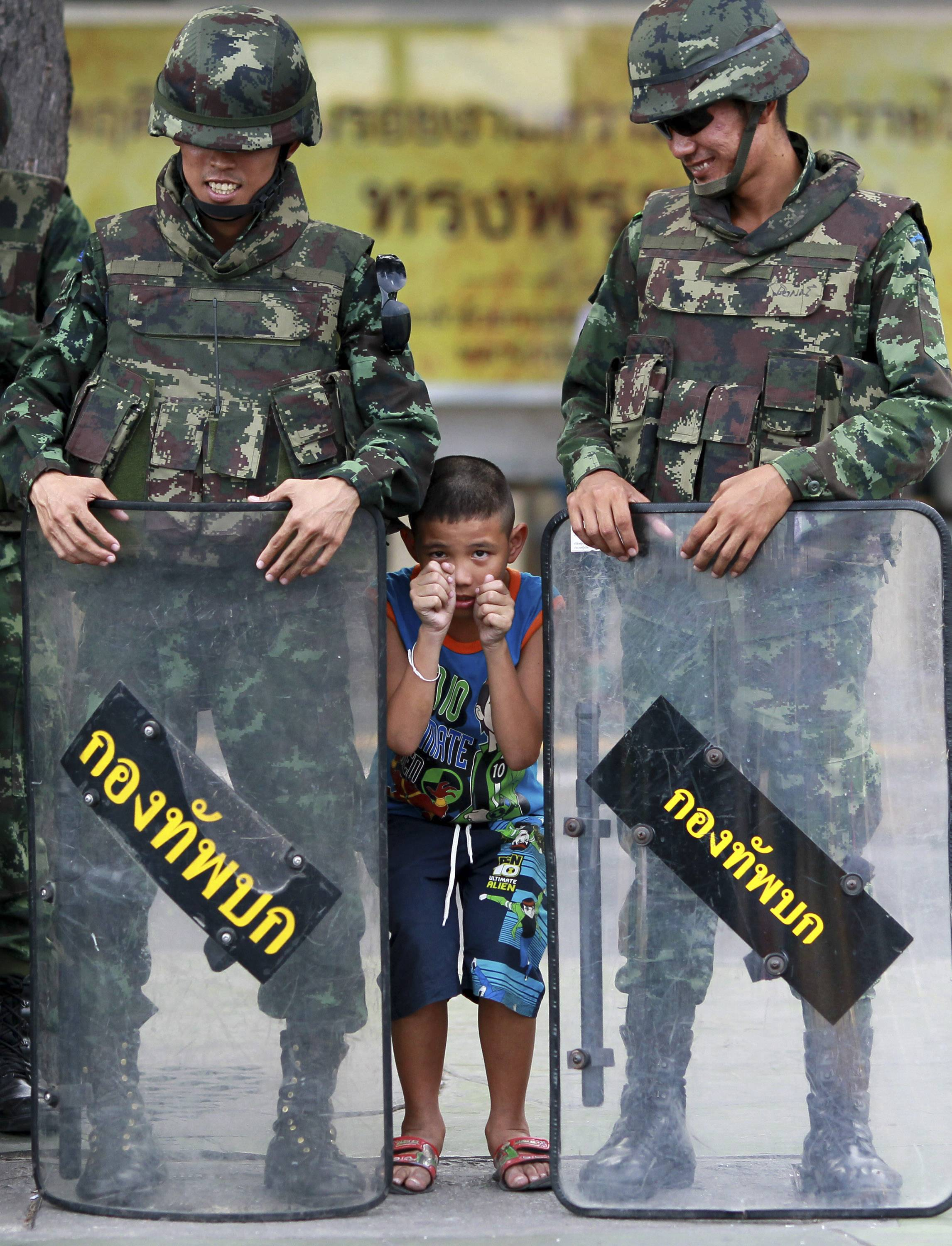 A boy, center, plays with Thai soldiers Friday guarding the square at Victory Monument to prevent anti-coup demonstration in Bangkok, Thailand.