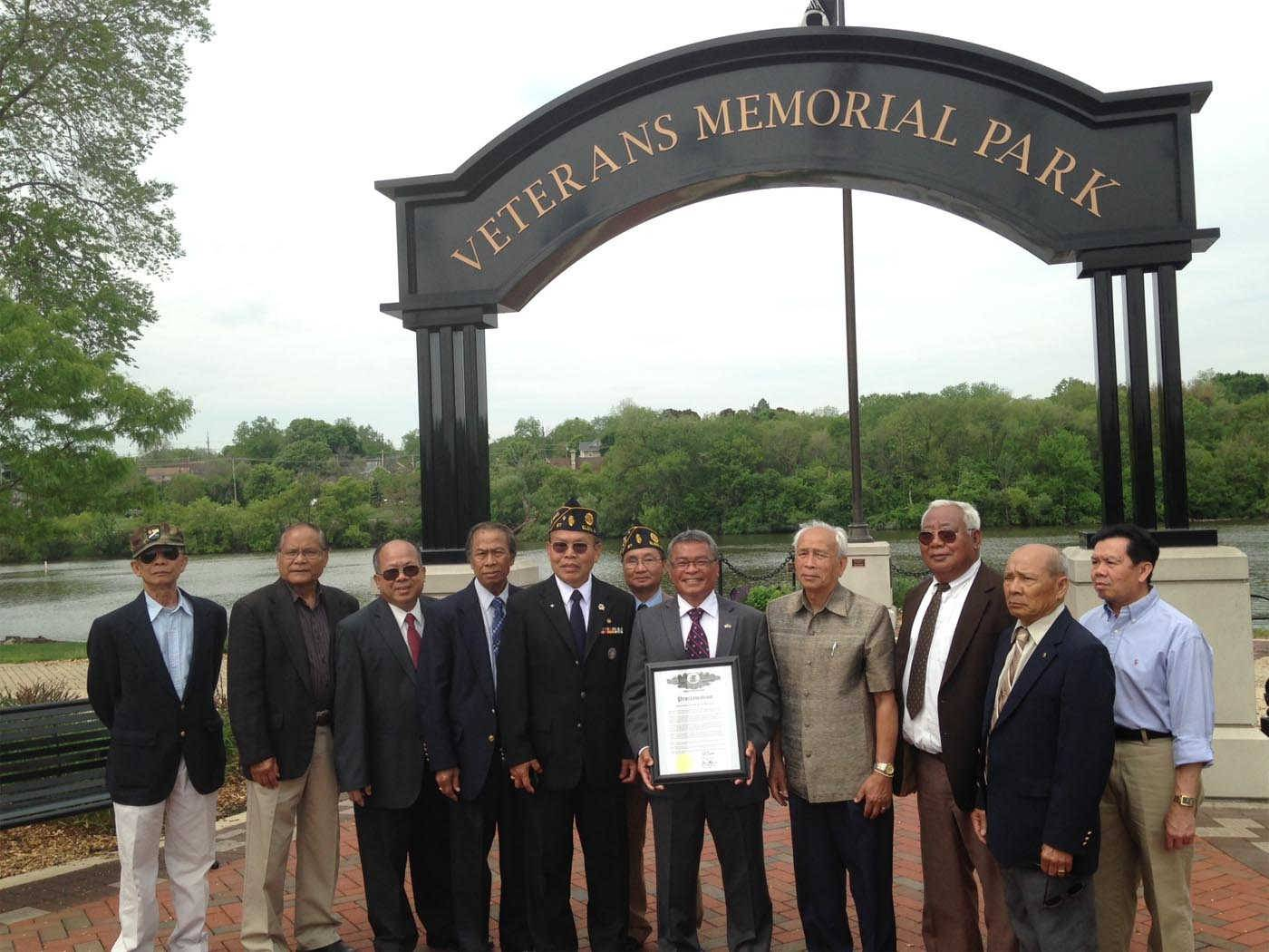 Elgin veteran Chindavanh Keomuongchanh, Illinois' veteran of the month for May, is pictured holding a plaque flanked by other Laotian veterans at a ceremony Wednesday at Veterans Memorial Park in Elgin.