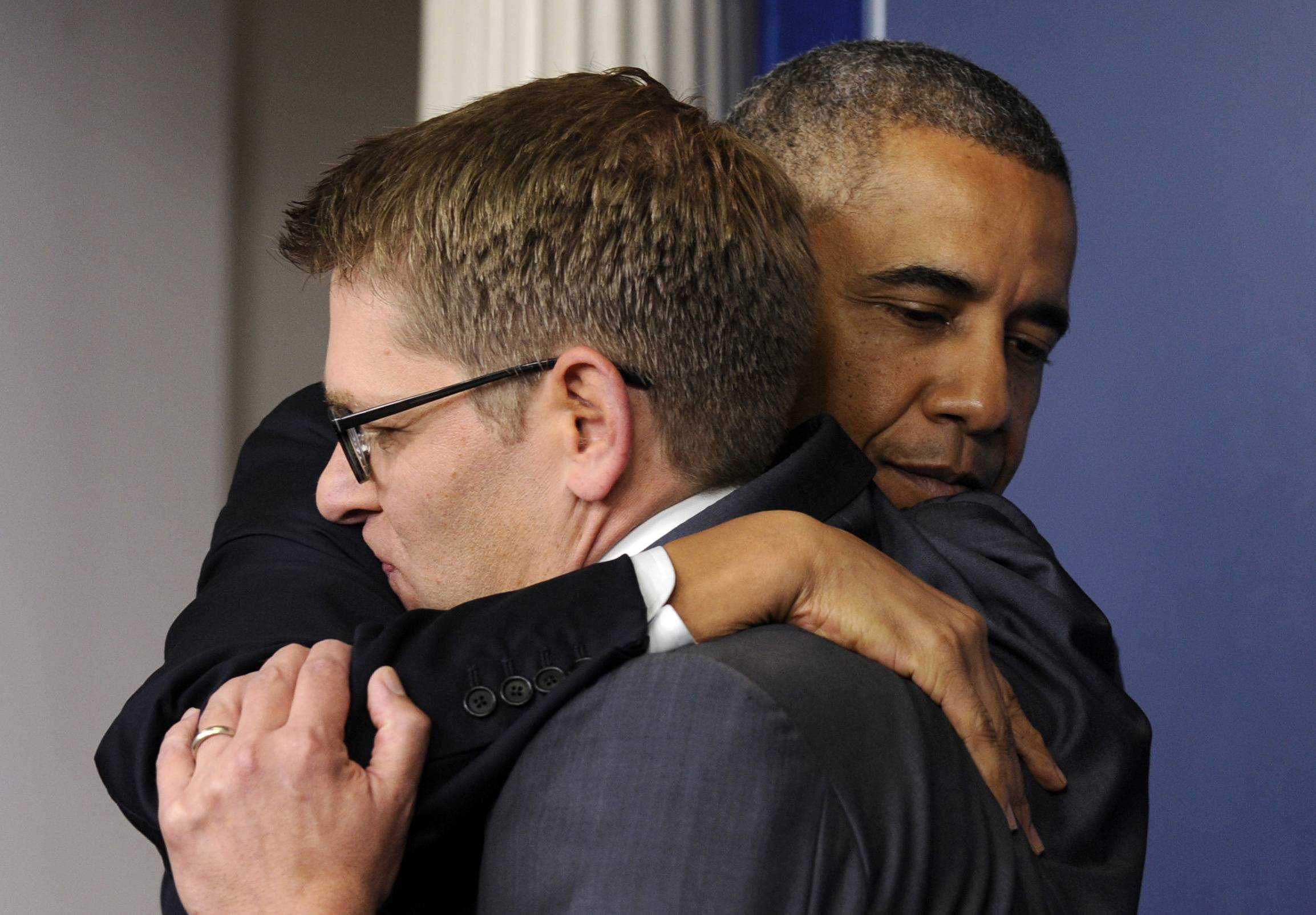 President Barack Obama gives White House press secretary Jay Carney a hug after announcing that Carney will step down later next month, during a surprise visit Friday to the Brady Press Briefing Room of the White House.
