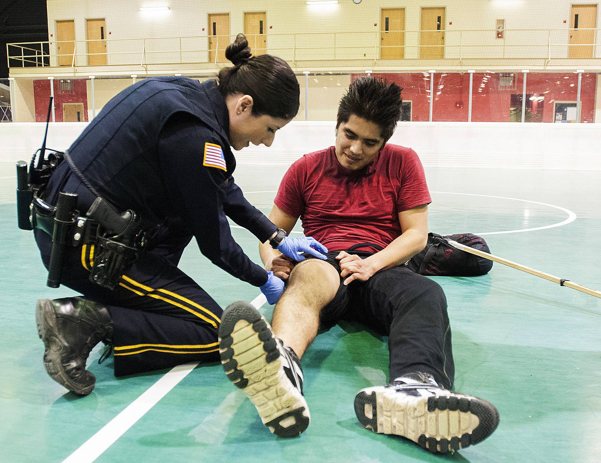 Northern Illinois University police officer Maria Christiansen checks on NIU senior Juan Martinez during a floor hockey game in April before calling paramedics to assist. Christiansen, a survivor of the Feb. 14, 2008, campus shooting, works the night shift on campus patrol.